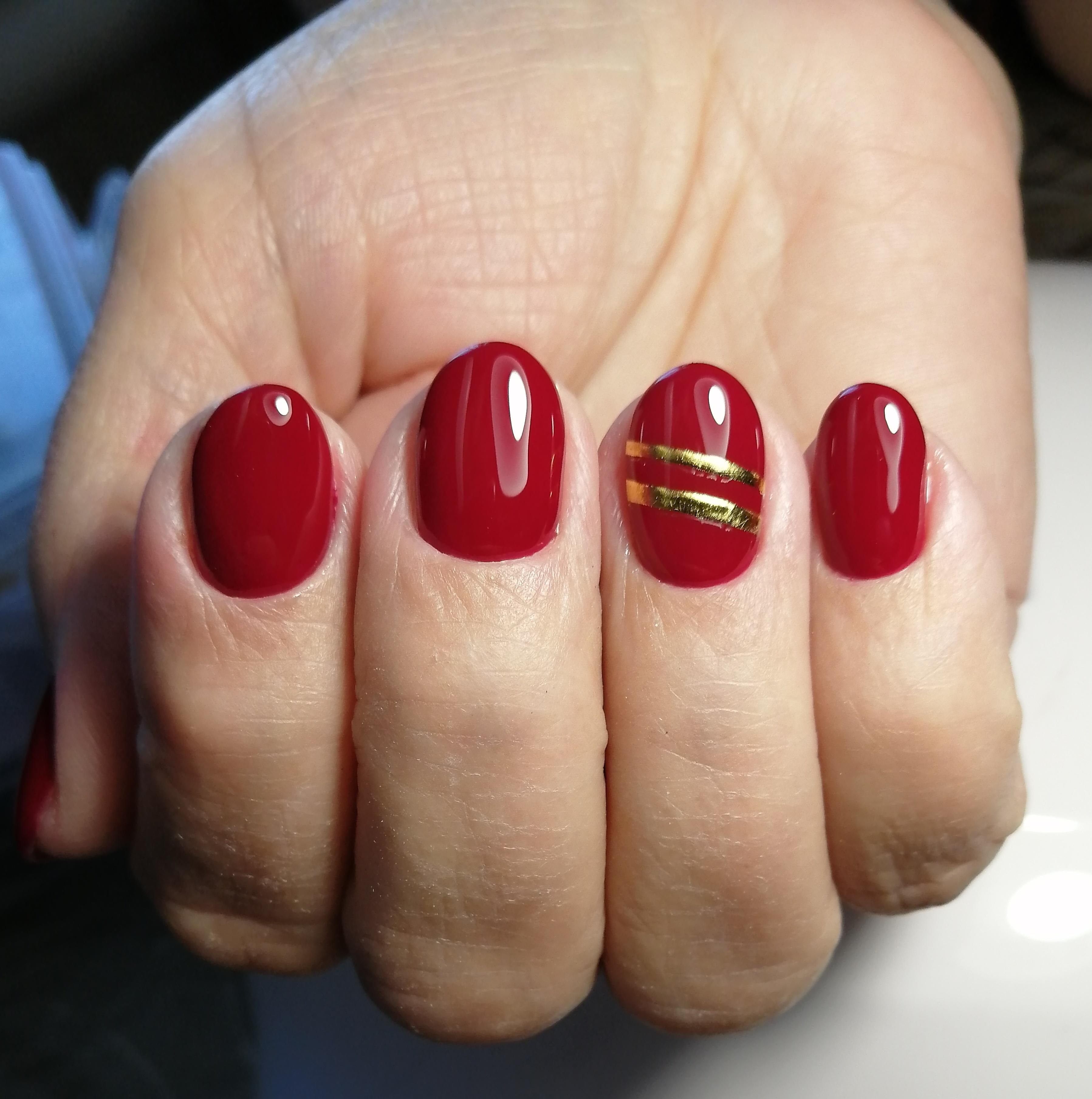 Маникюр с золотыми полосками в темно-красном цвете.