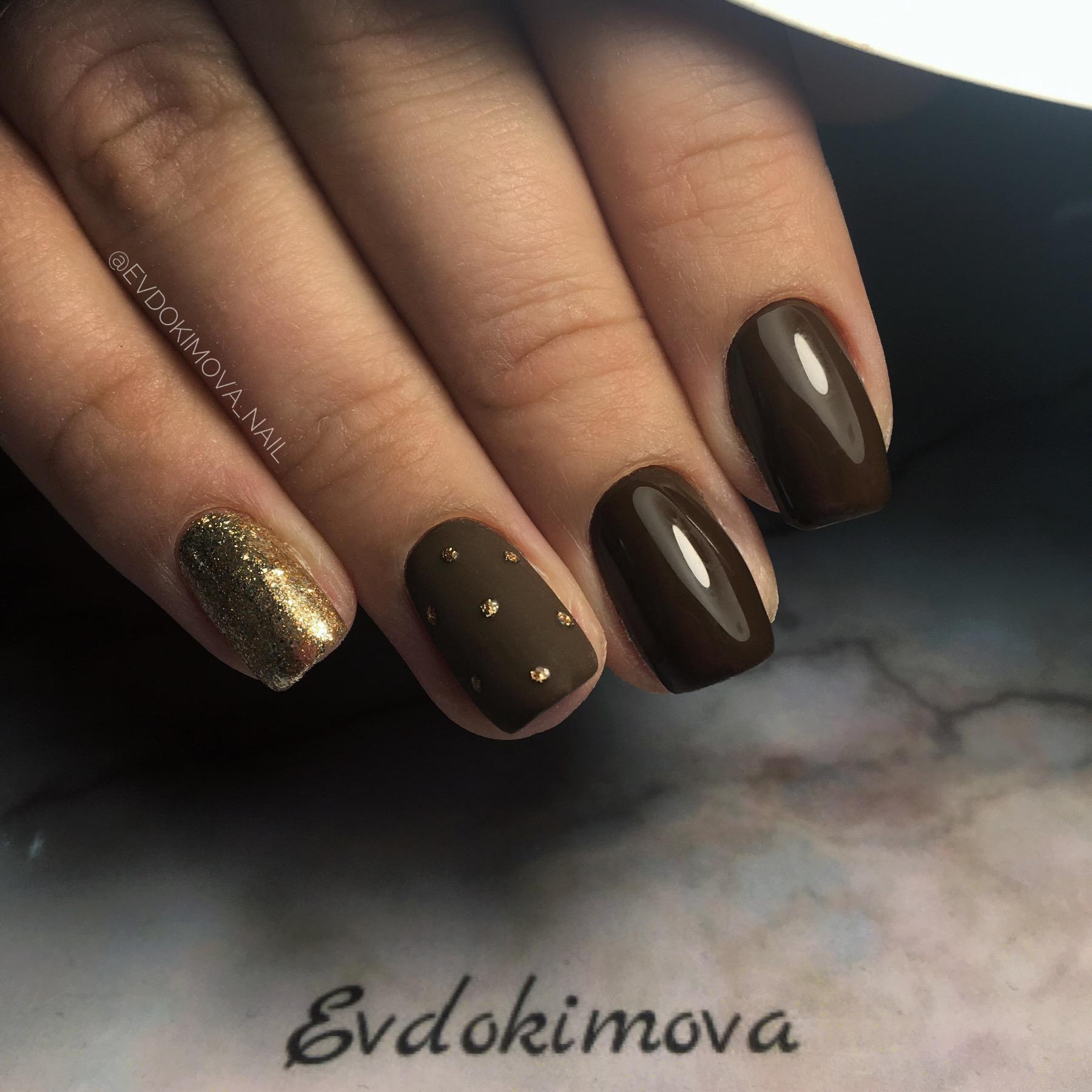 Маникюр с золотыми блестками в шоколадном цвете.
