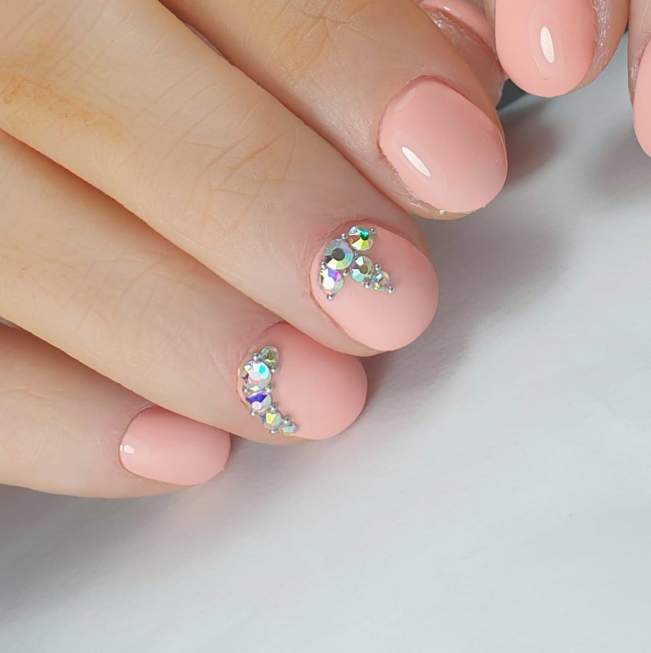 Маникюр со стразами в персиковом цвете на короткие ногти.
