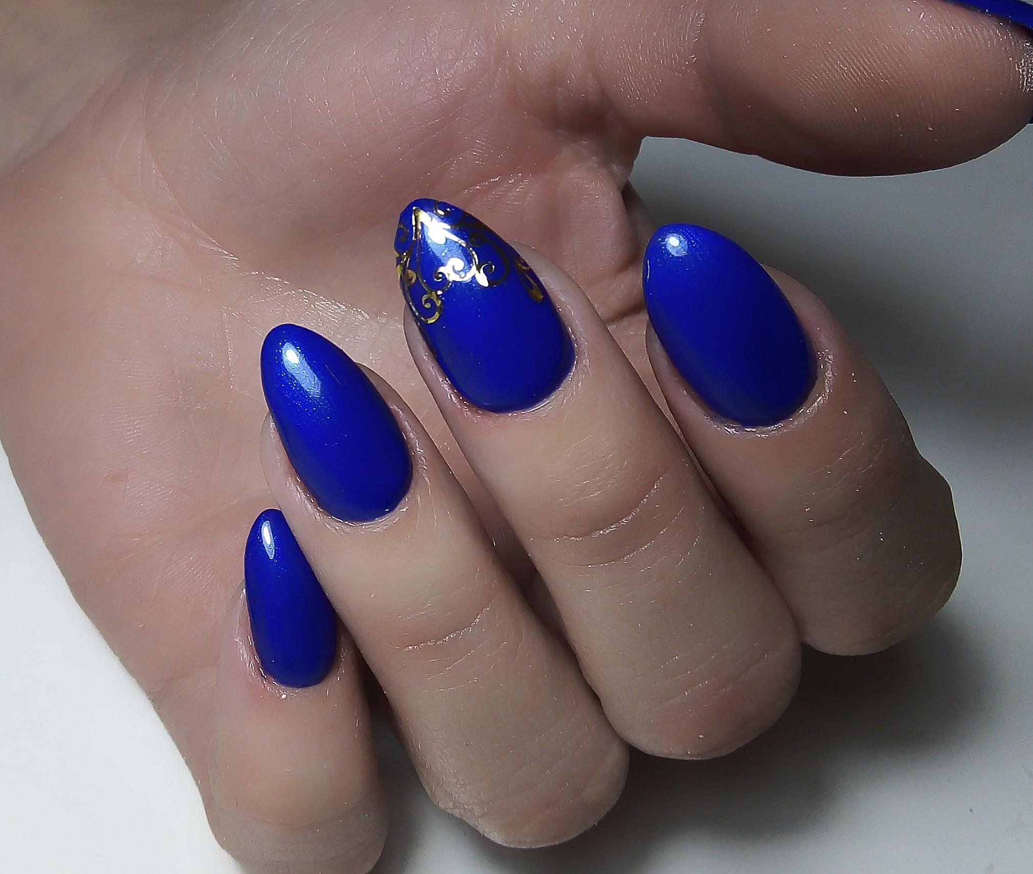 Маникюр с золотыми вензелями в синем цвете.