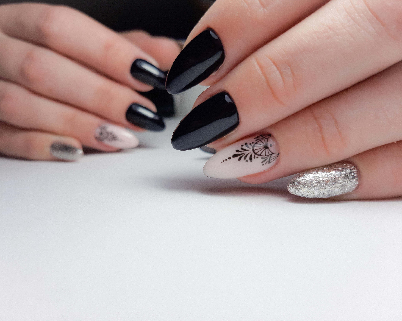 Маникюр с этническим слайдером и серебряными блестками в черном цвете.