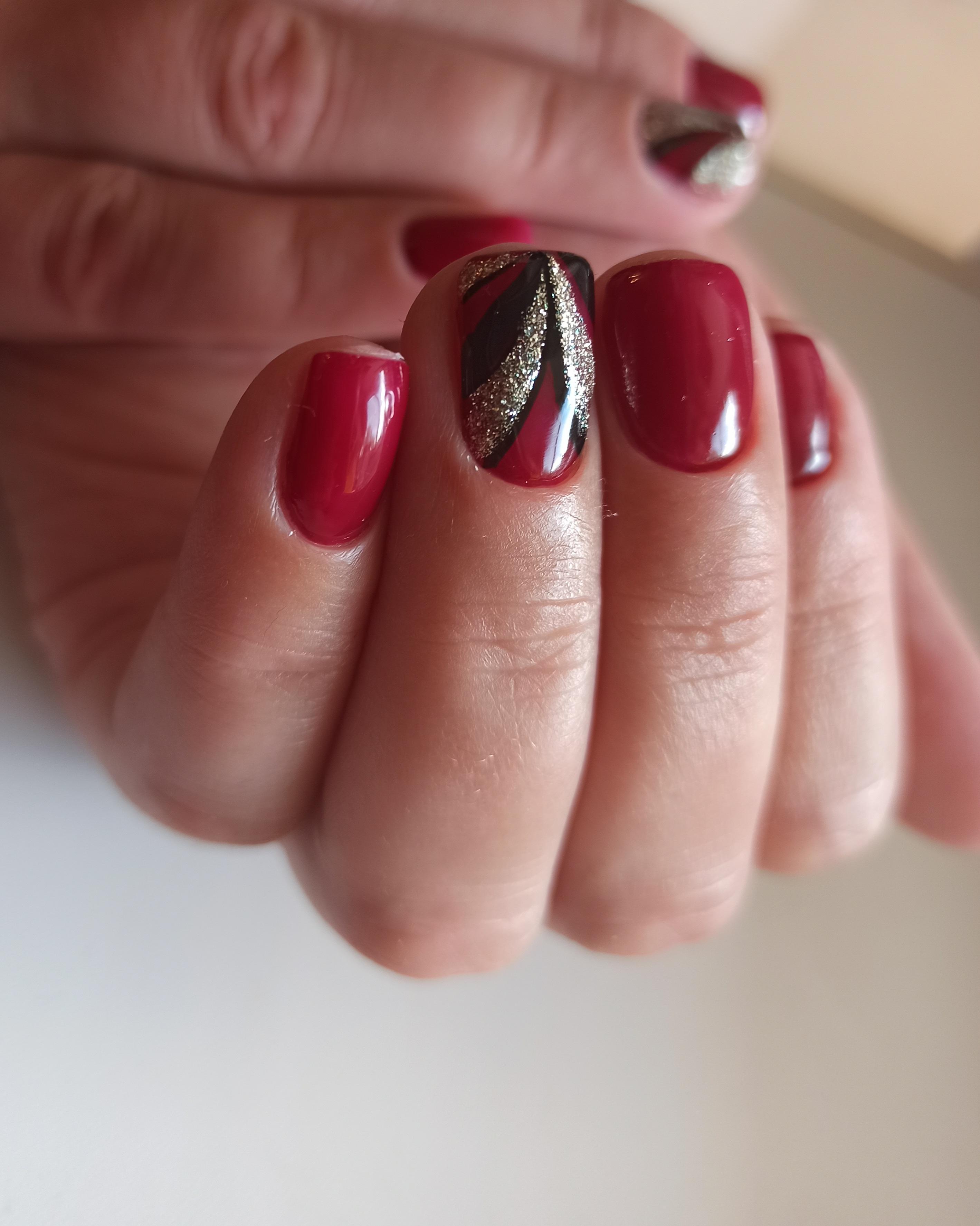 Маникюр с рисунком и блестками в бордовом цвете на короткие ногти.