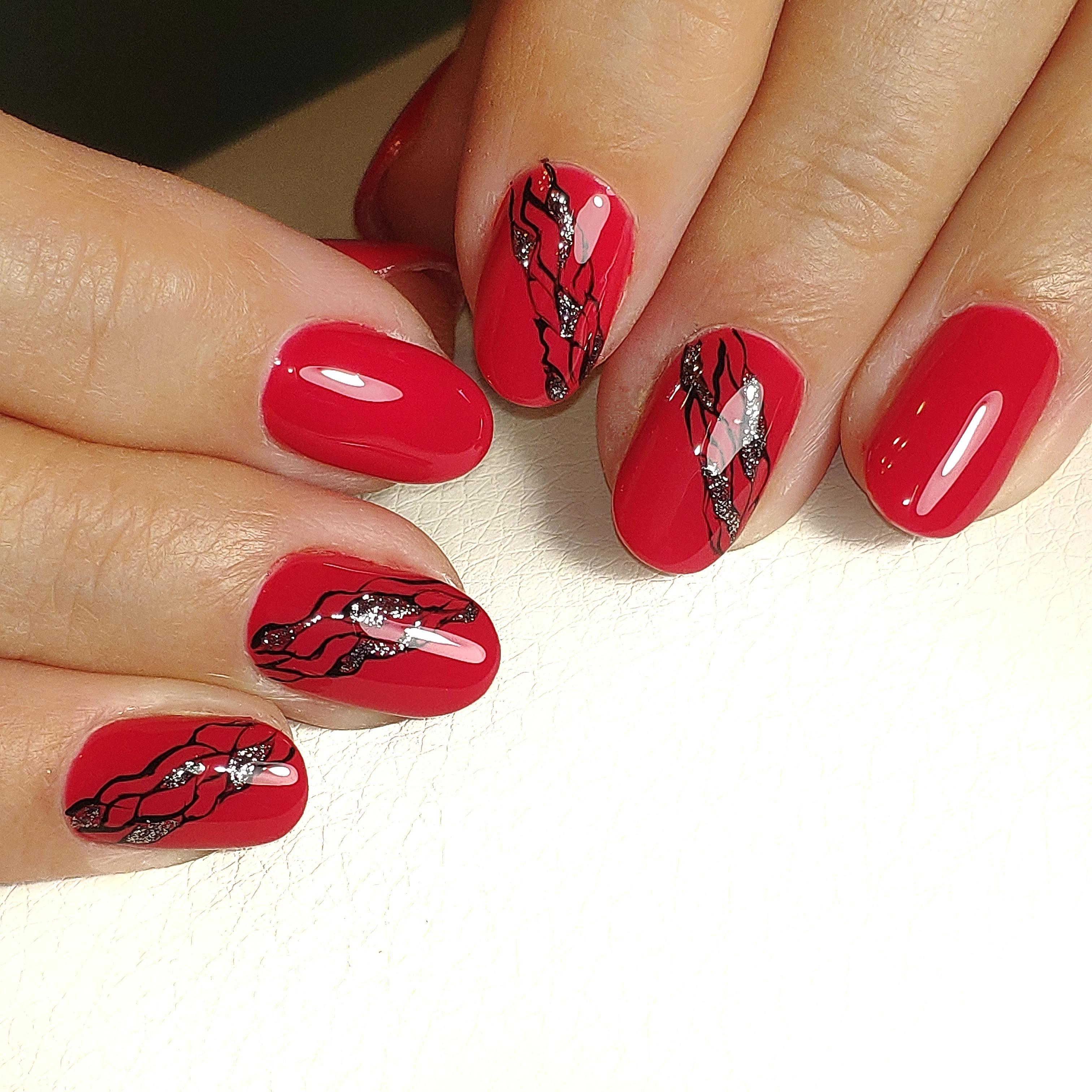 Однотонный маникюр в красном цвете с абстрактным рисунком и блёстками.