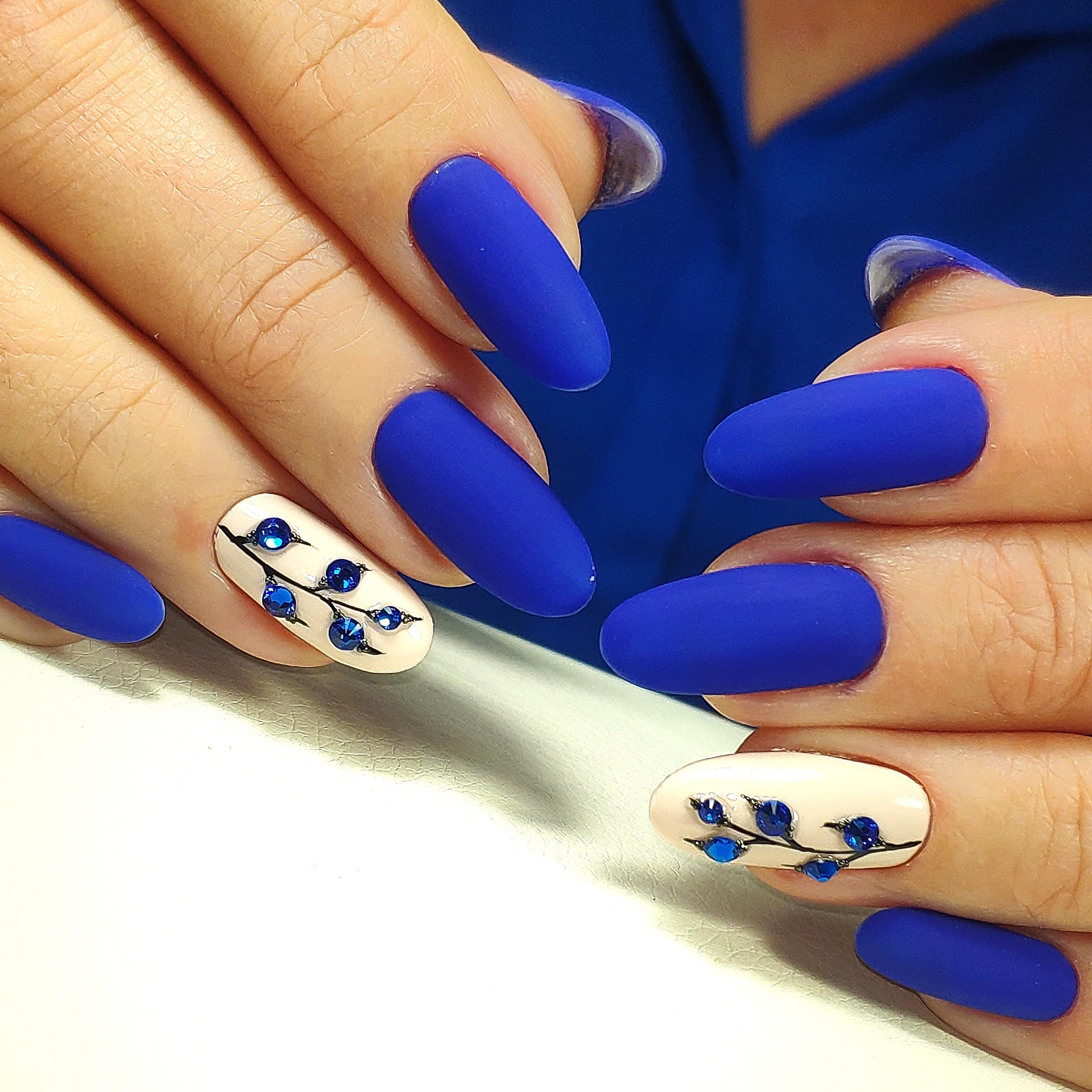Матовый маникюр в синем цвете с белым дизайном, растительным рисунком и синими стразами.
