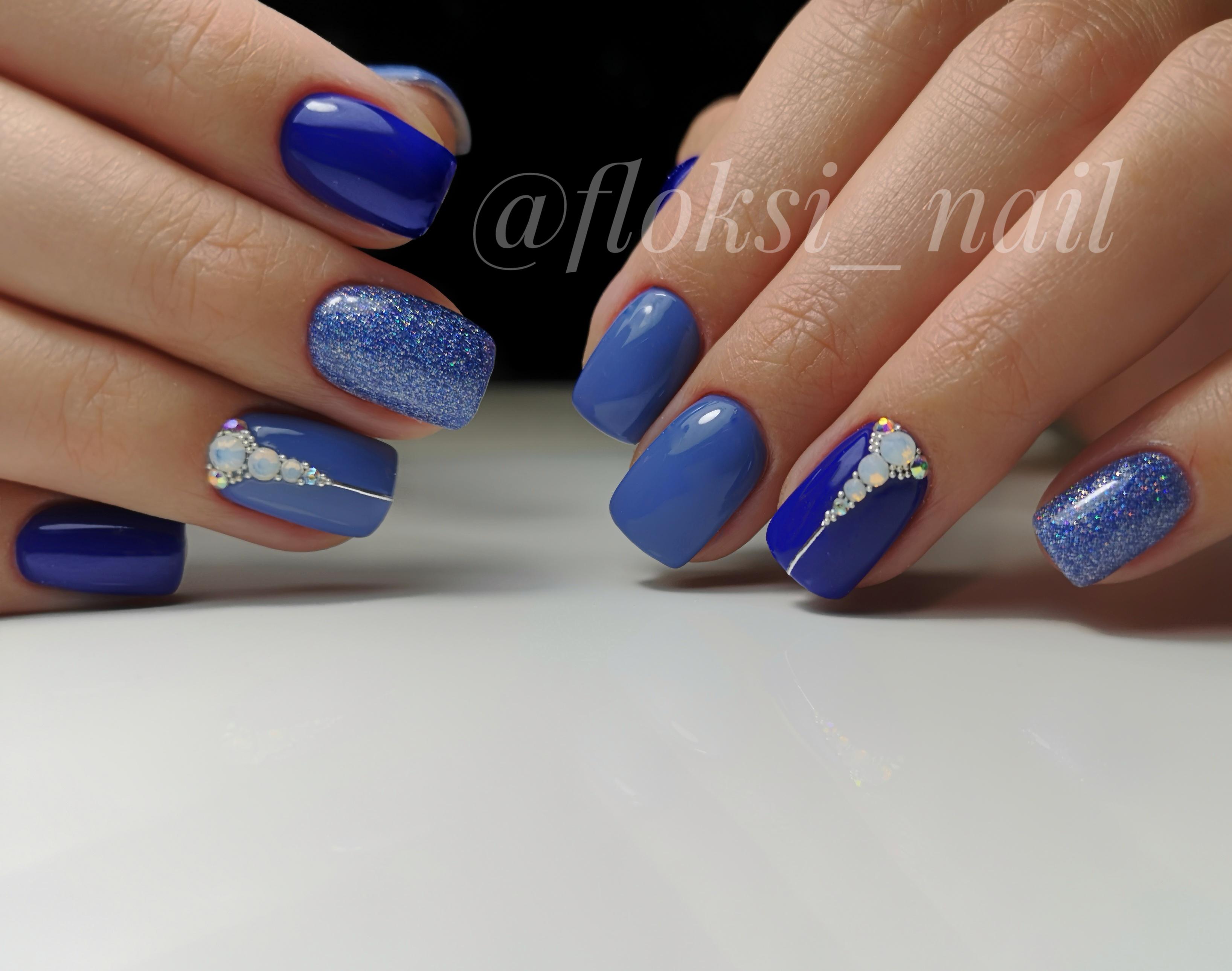 Маникюр в синем цвете с блёстками и стразами.