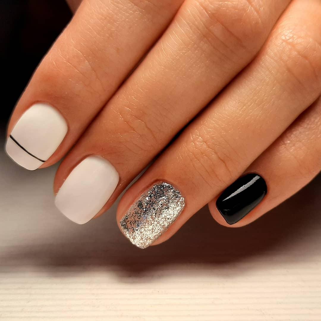 Маникюр с серебряными блестками в белом цвете на короткие ногти.