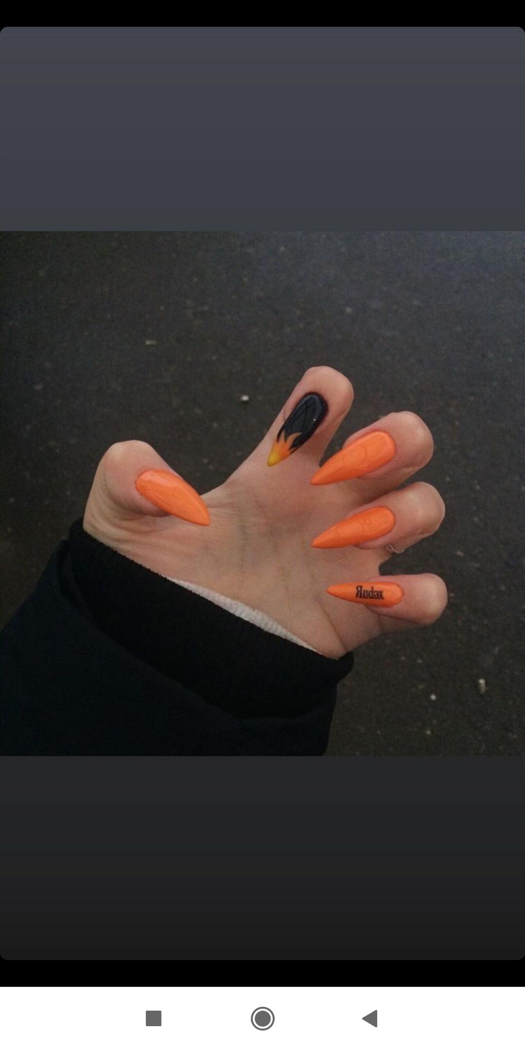 Маникюр с языками пламени и надписями в оранжевом цвете на длинные ногти.