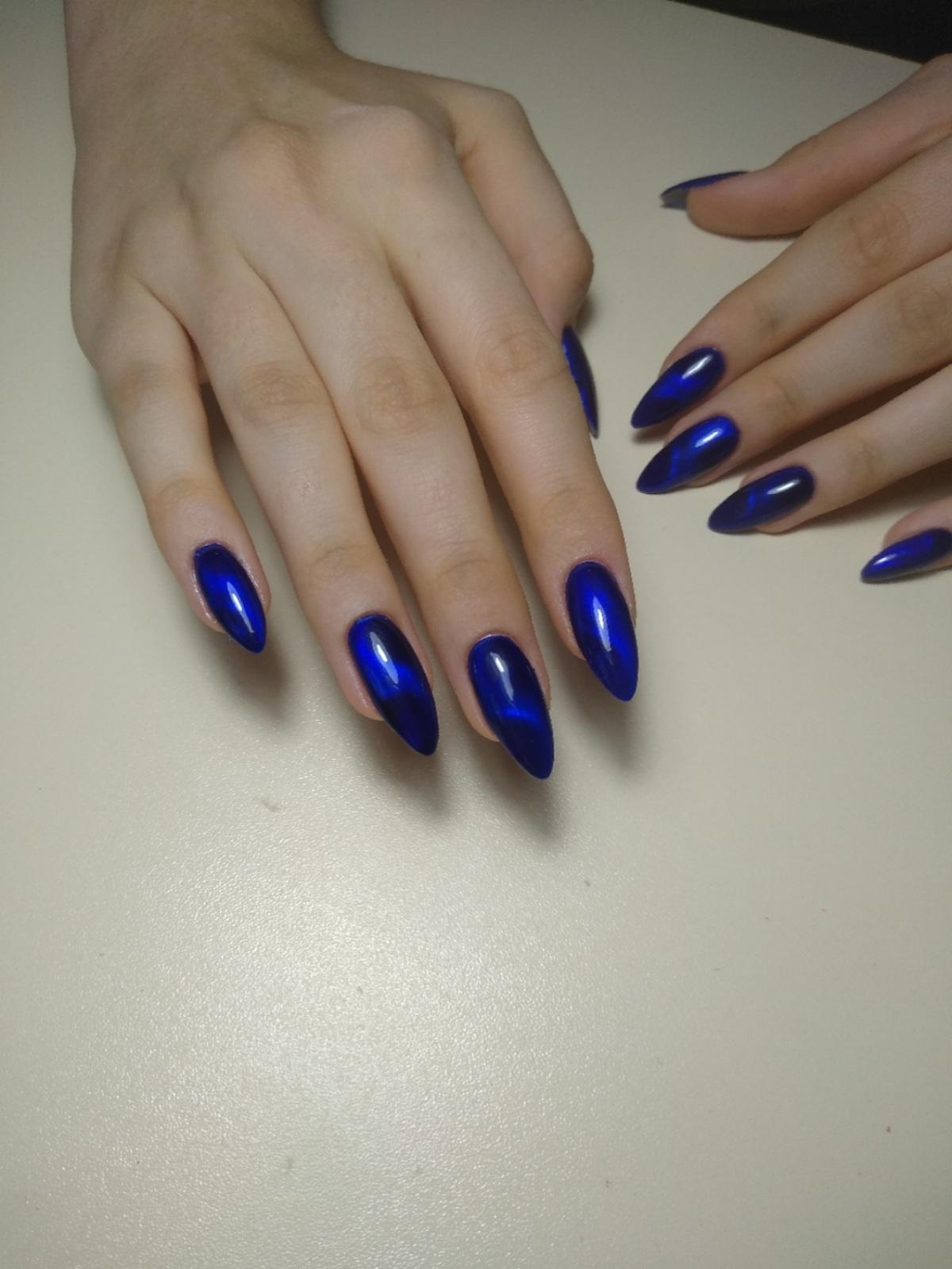 Маникюр в тёмно-синем цвете с эффектом кошачий глаз.