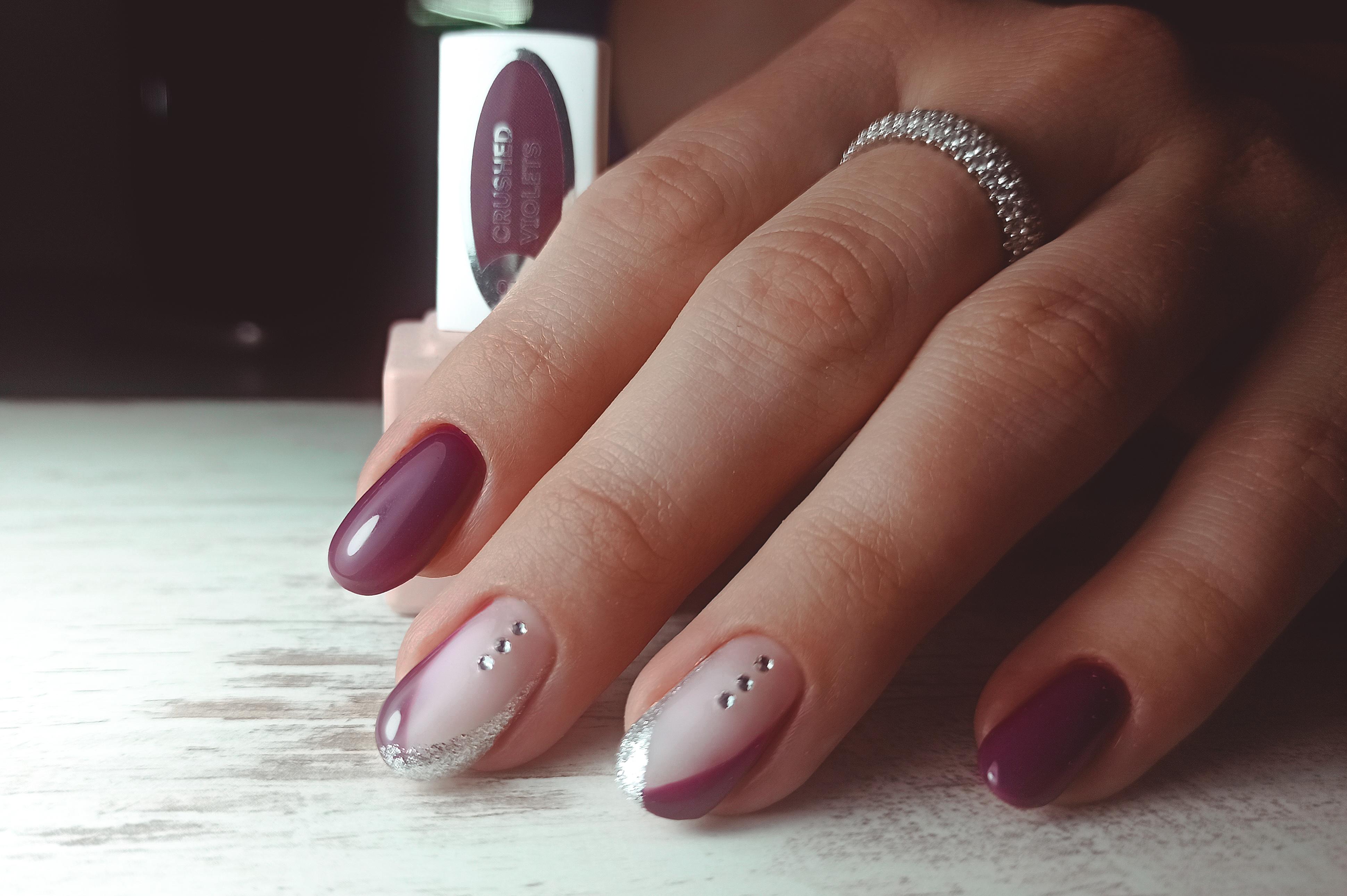 Маникюр с френч-дизайном и стразами в баклажановом цвете на короткие ногти.