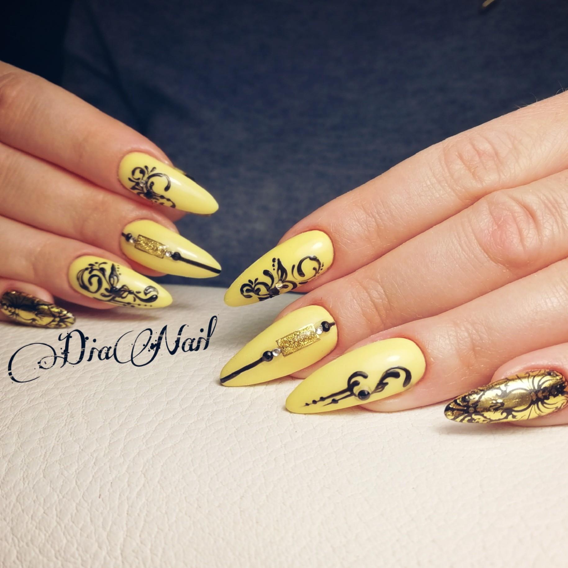 Маникюр с вензелями и золотыми блестками в желтом цвете.