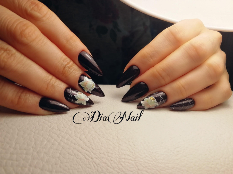 Маникюр с цветочным рисунком с блестками в черном цвете.