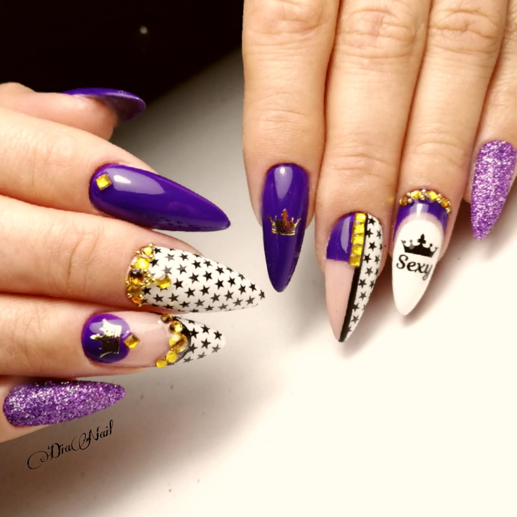Маникюр со звездочками, слайдерами, стразами и надписями в фиолетовом цвете.