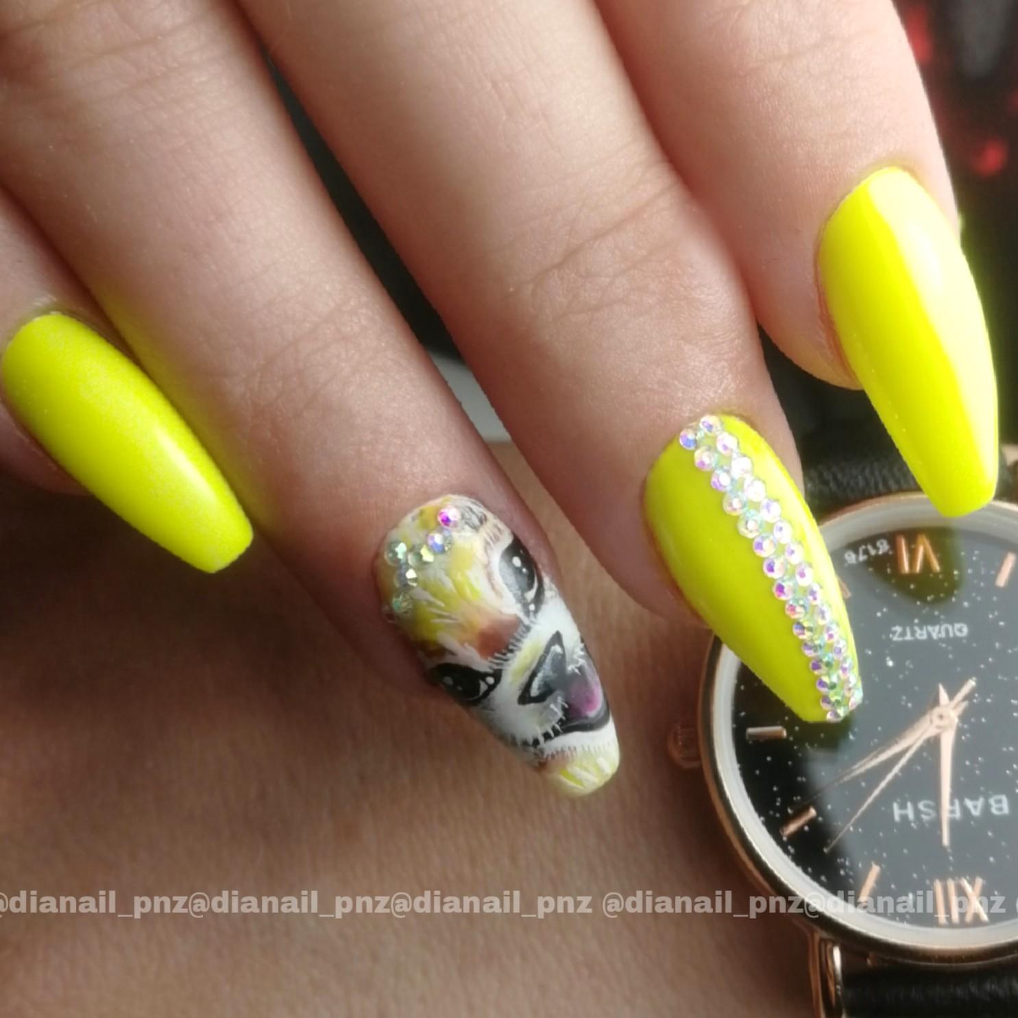Маникюр с рисунком и стразами в желтом цвете на длинные ногти.