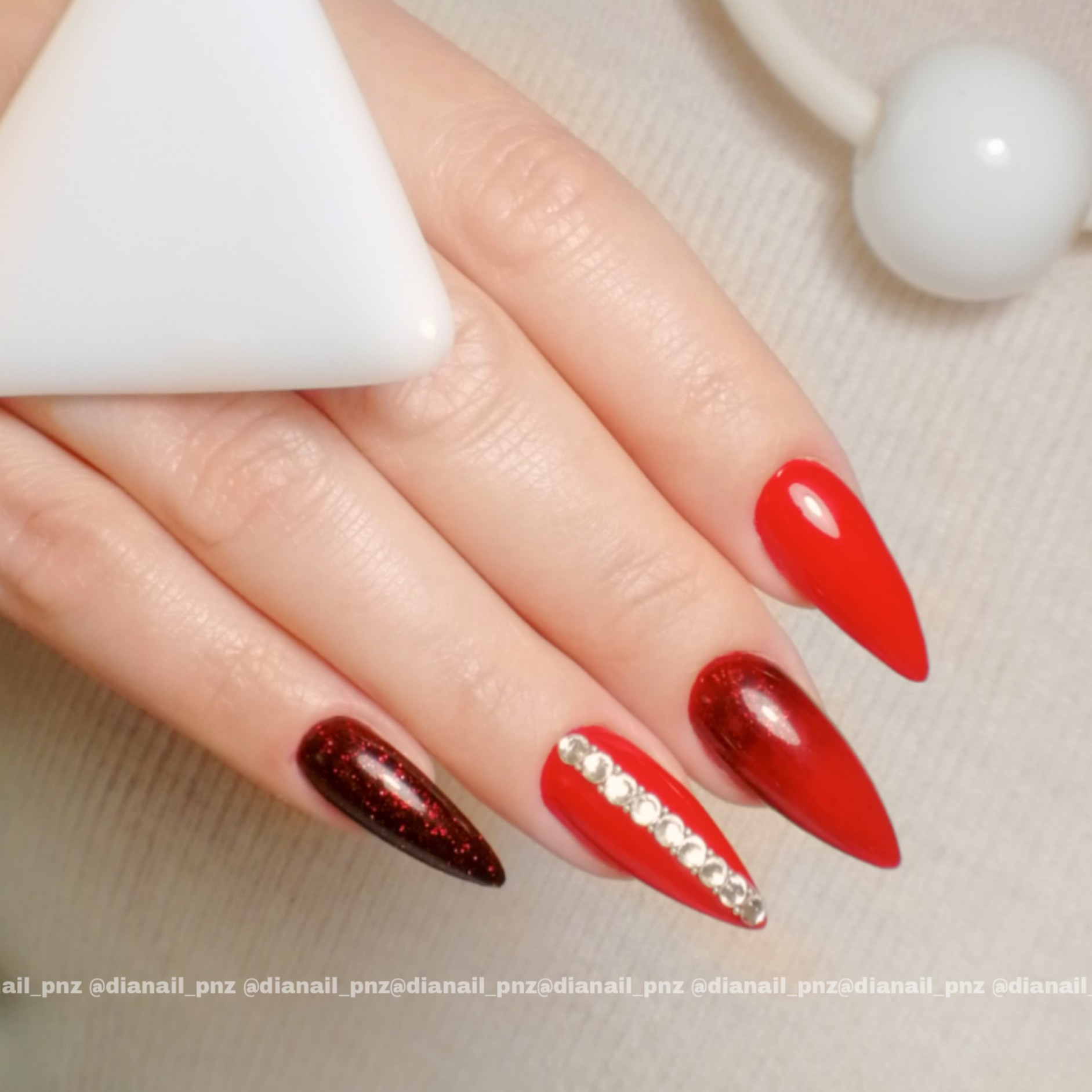 Маникюр с блестками и стразами в красном цвете на длинные ногти.
