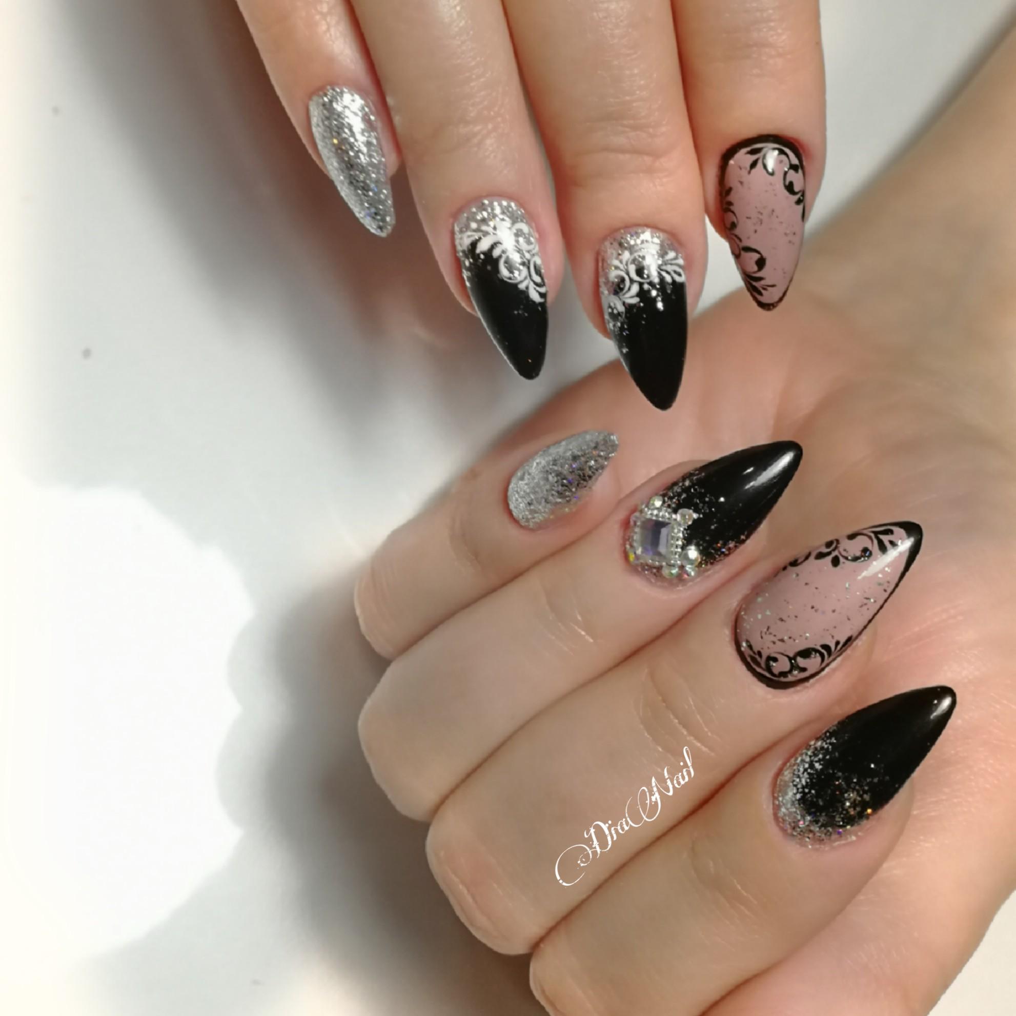 Маникюр с нюдовым дизайном, вензелями, серебряными блестками и стразами в черном цвете.