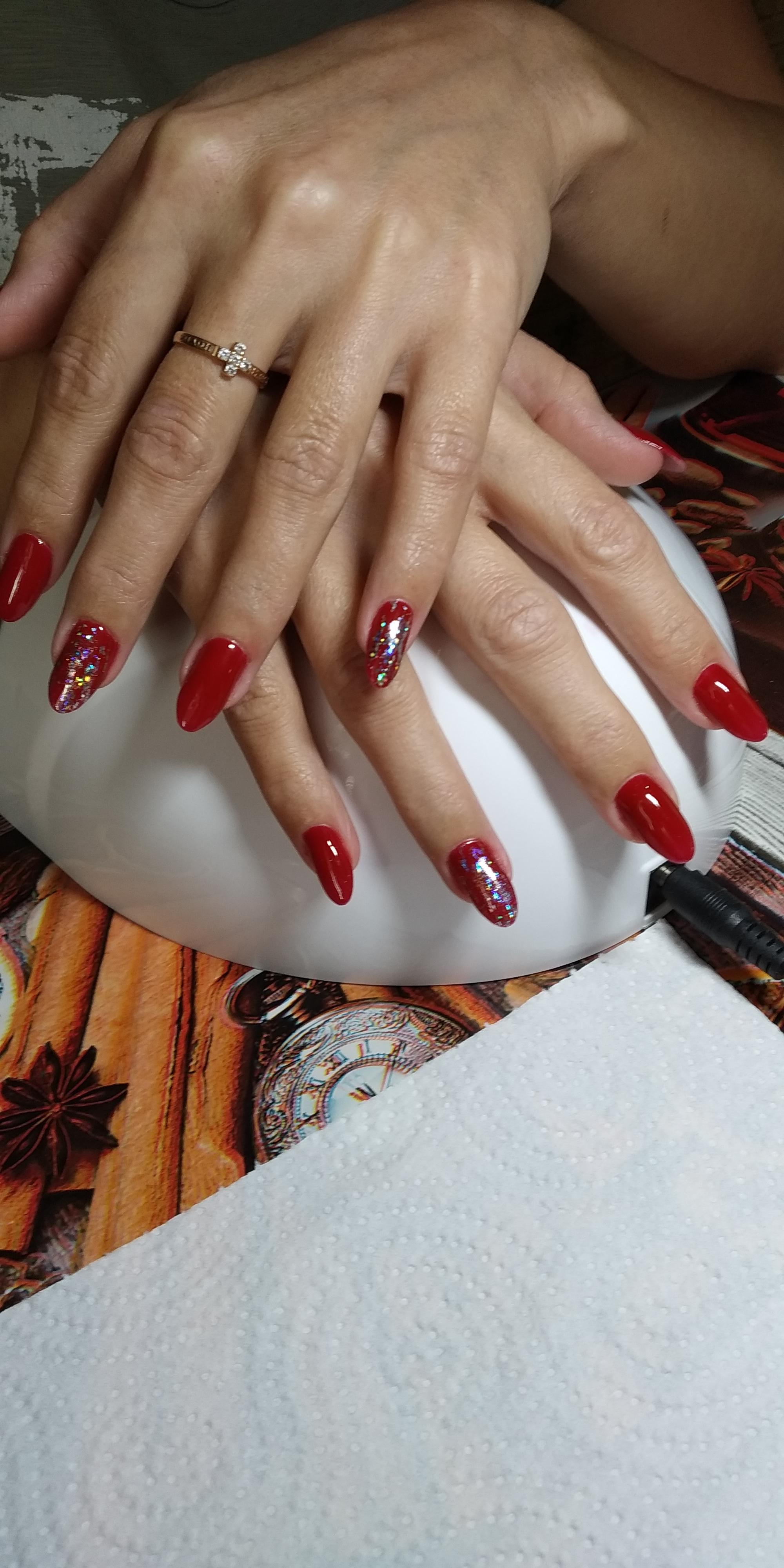 Однотонный маникюр в красном цвете с цветными блёстками.