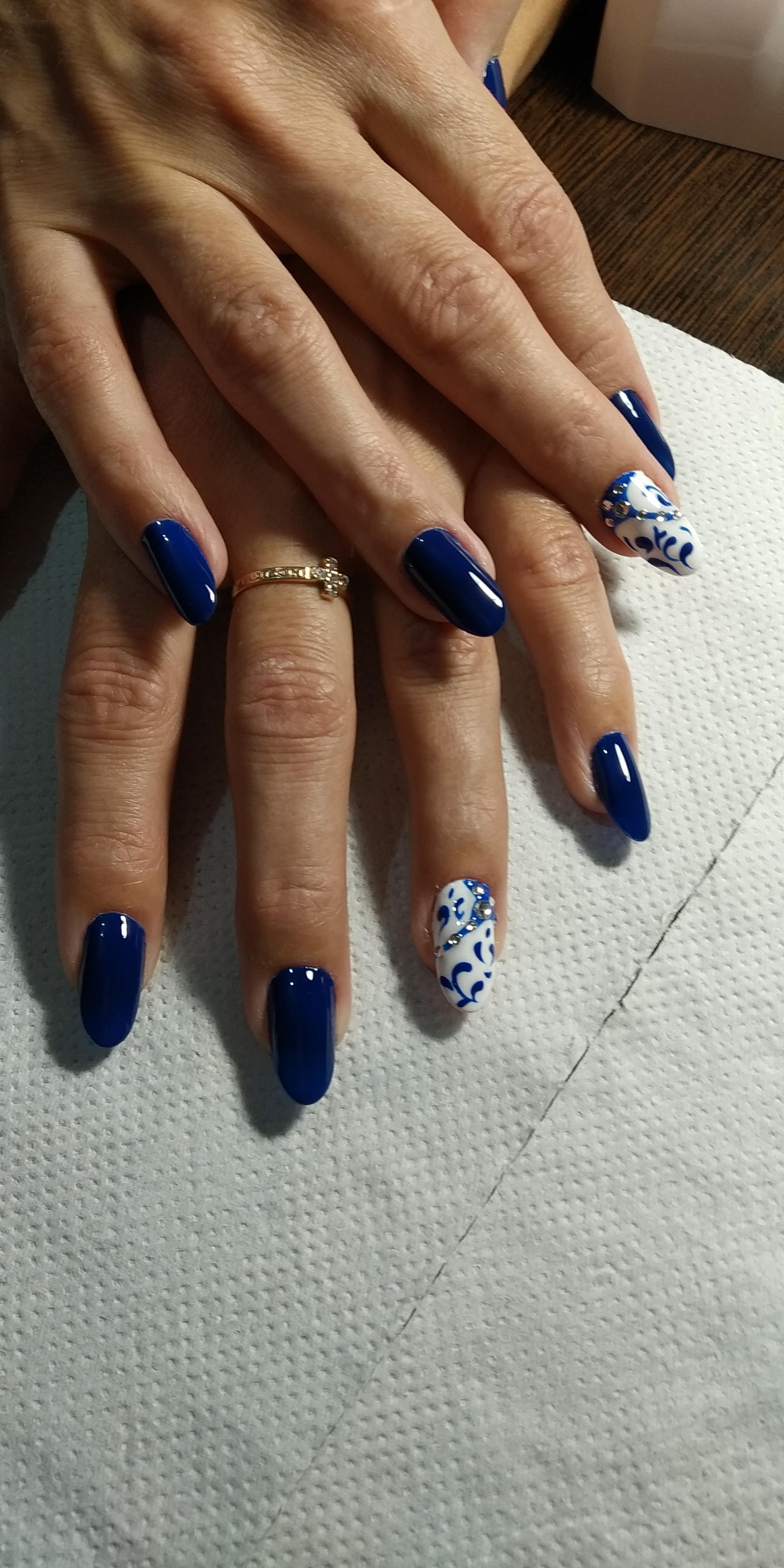 Маникюр в тёмно-синем цвете с контрастным белым дизайном, с синими вензелями и стразами.