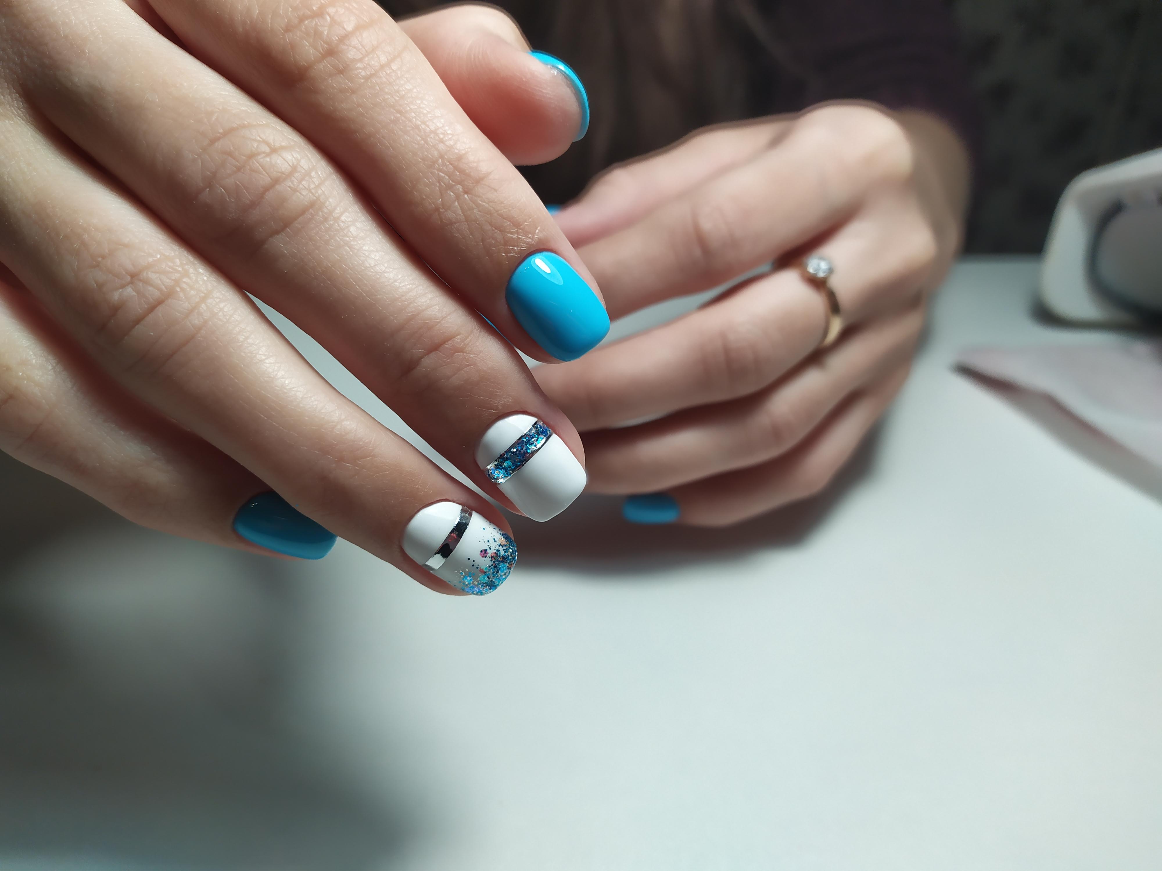 Маникюр с блестками и серебряными полосками в голубом цвете.