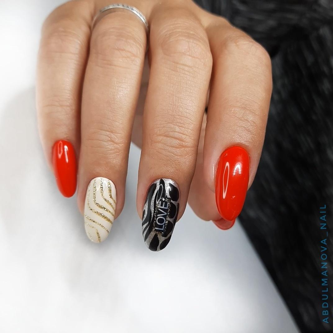 Маникюр с блестками и надписями в красном цвете на длинные ногти.