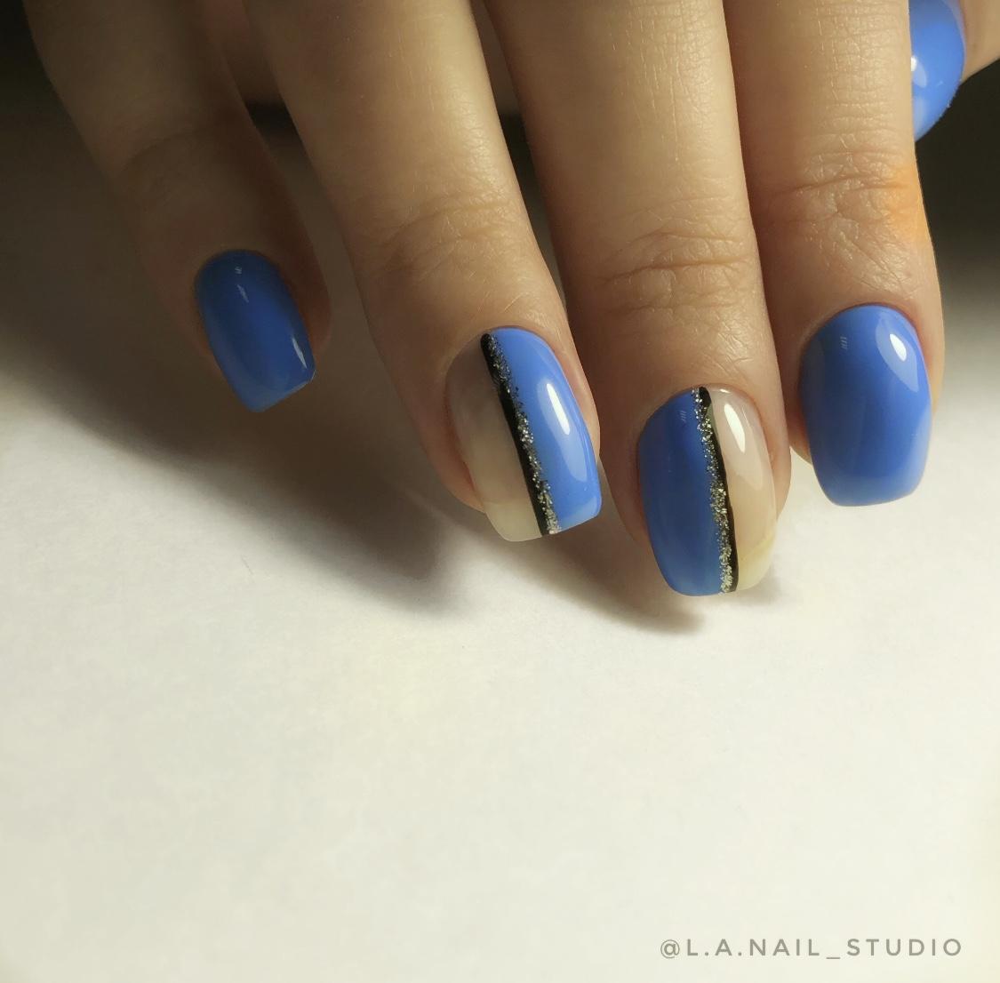 Маникюр в голубом цвете с нюдовым прозрачным дизайном, чёрными и золотыми полосками.