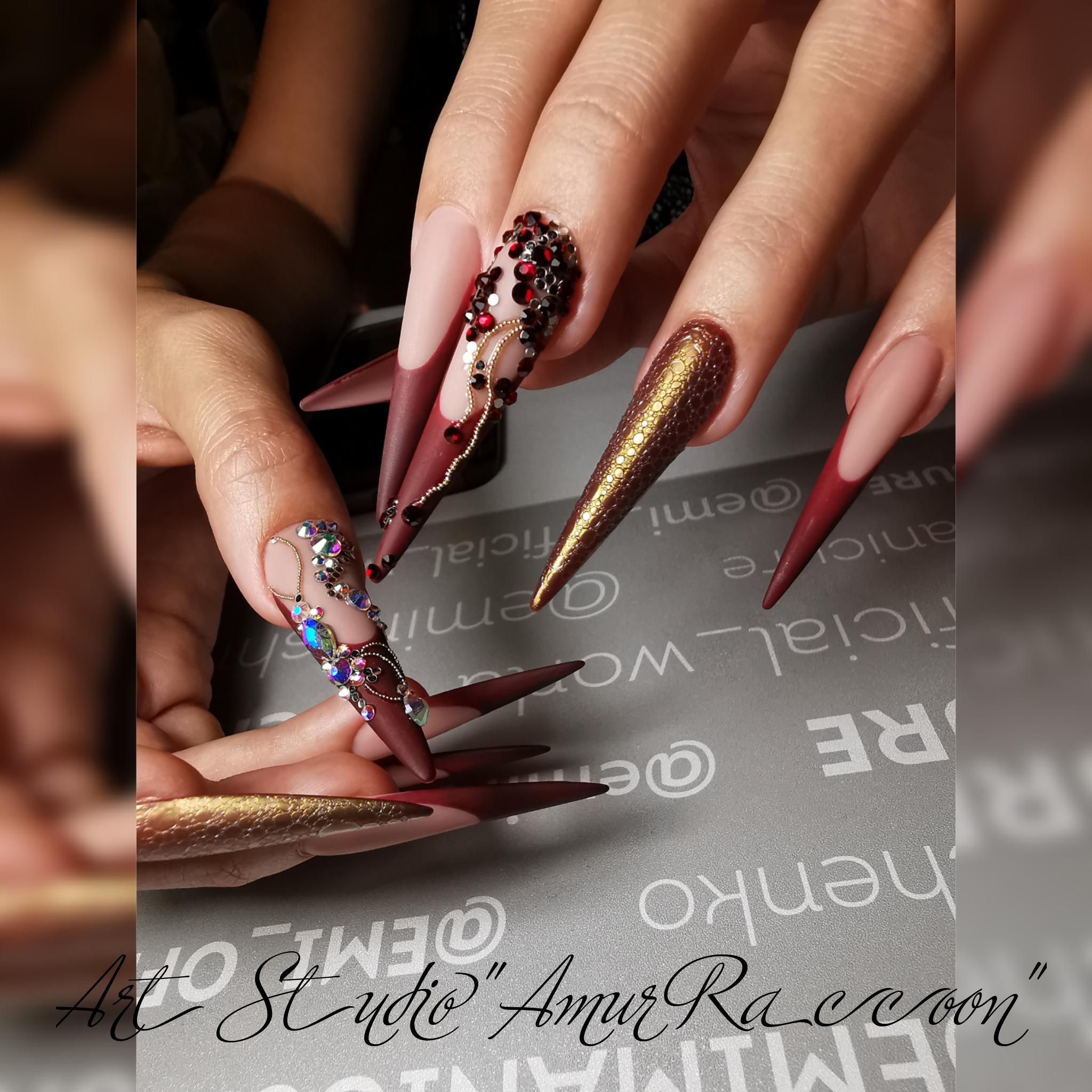 Бордовый матовый французский маникюр на длинных ногтях с объёмными стразами и золотыми блёстками.