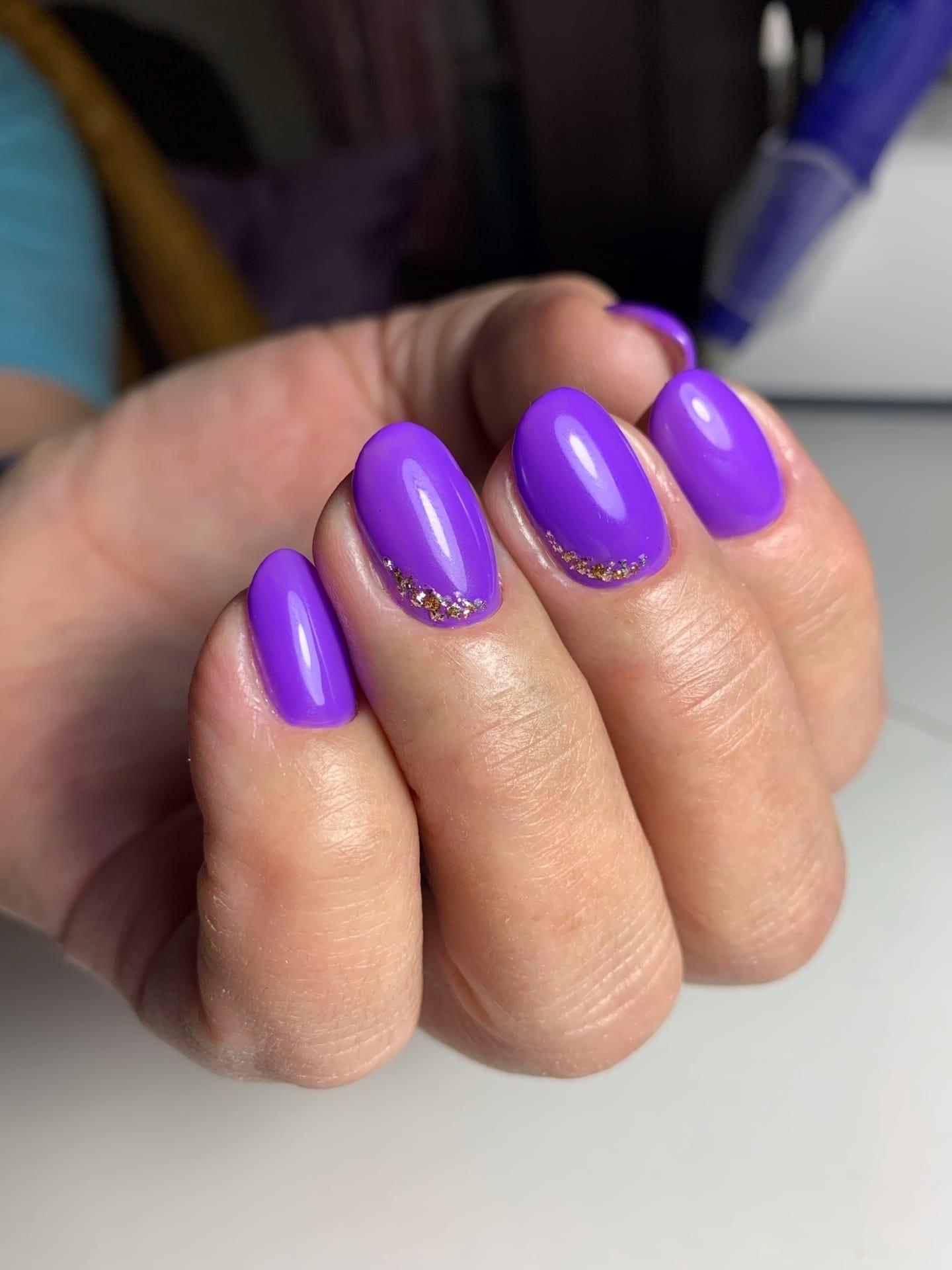 Маникюр с золотыми блестками в фиолетовом цвете на короткие ногти.