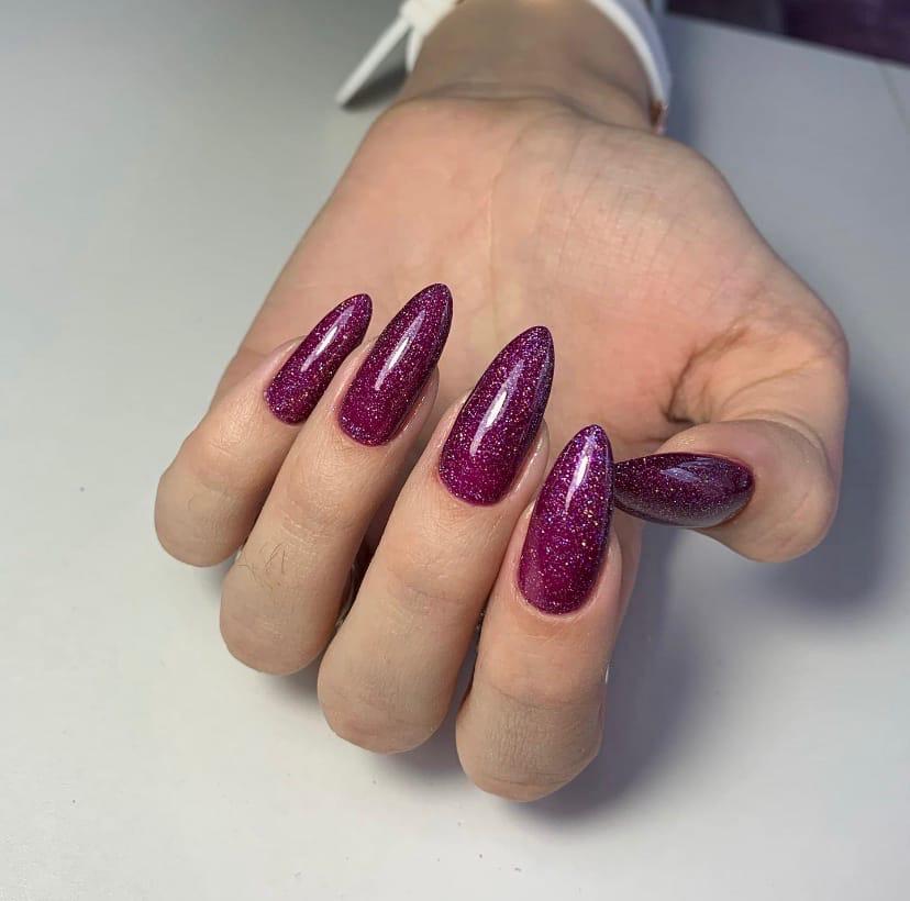 Маникюр с блестками в баклажановом цвете на длинные ногти.