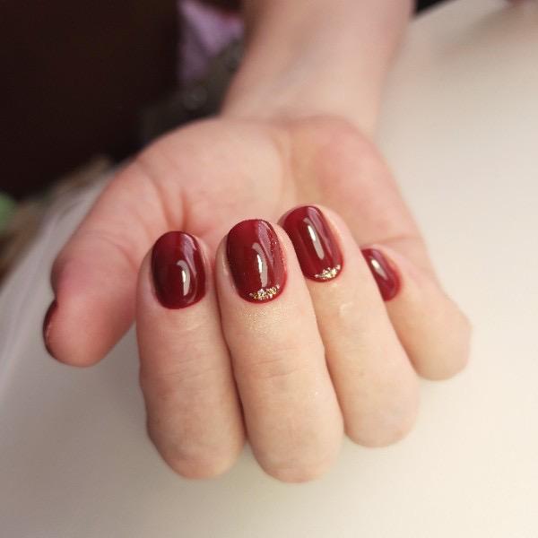 Маникюр с золотыми блестками в темно-красном цвете на короткие ногти.