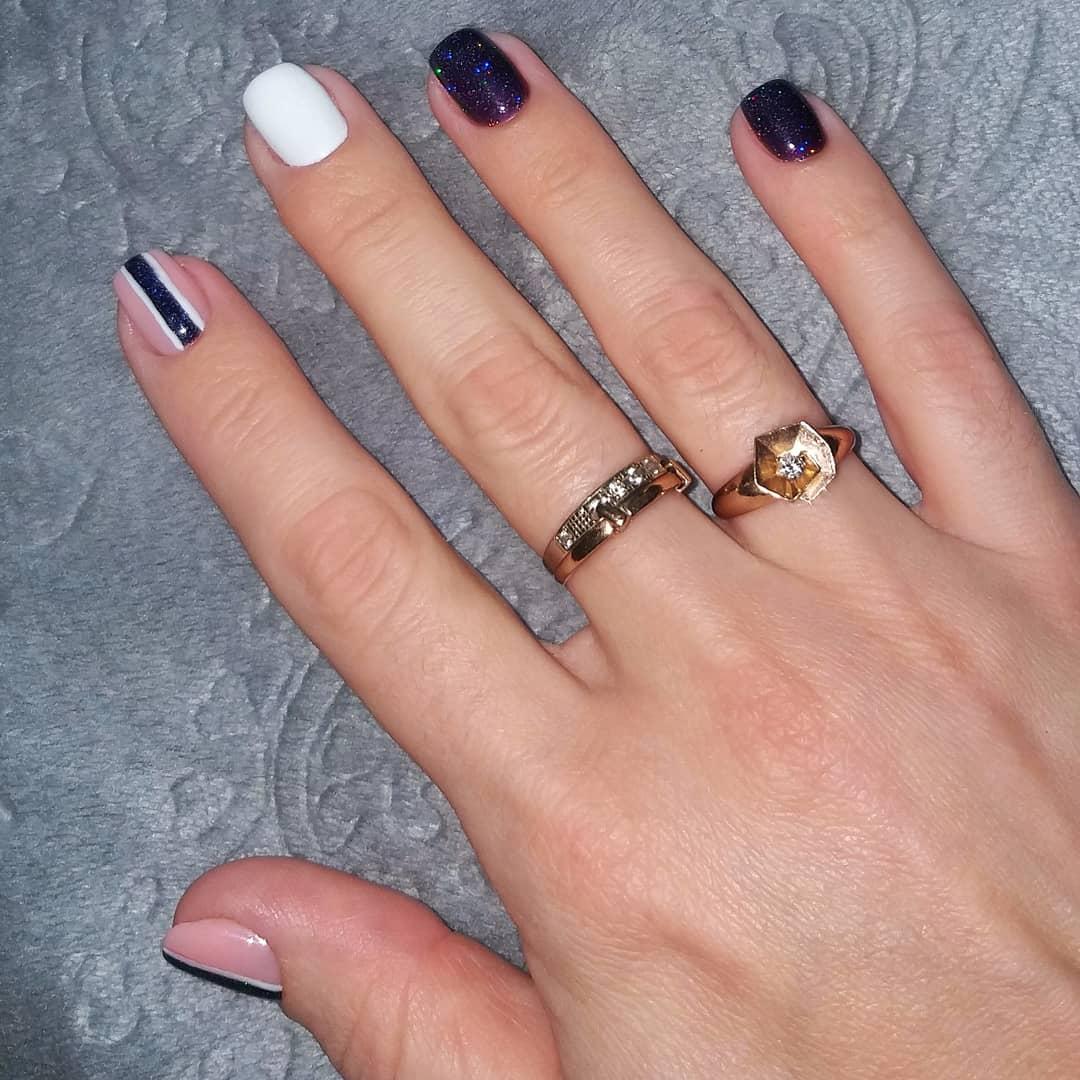 Маникюр в тёмно-синем цвете с блёстками, нюдовым дизайром и полосками.