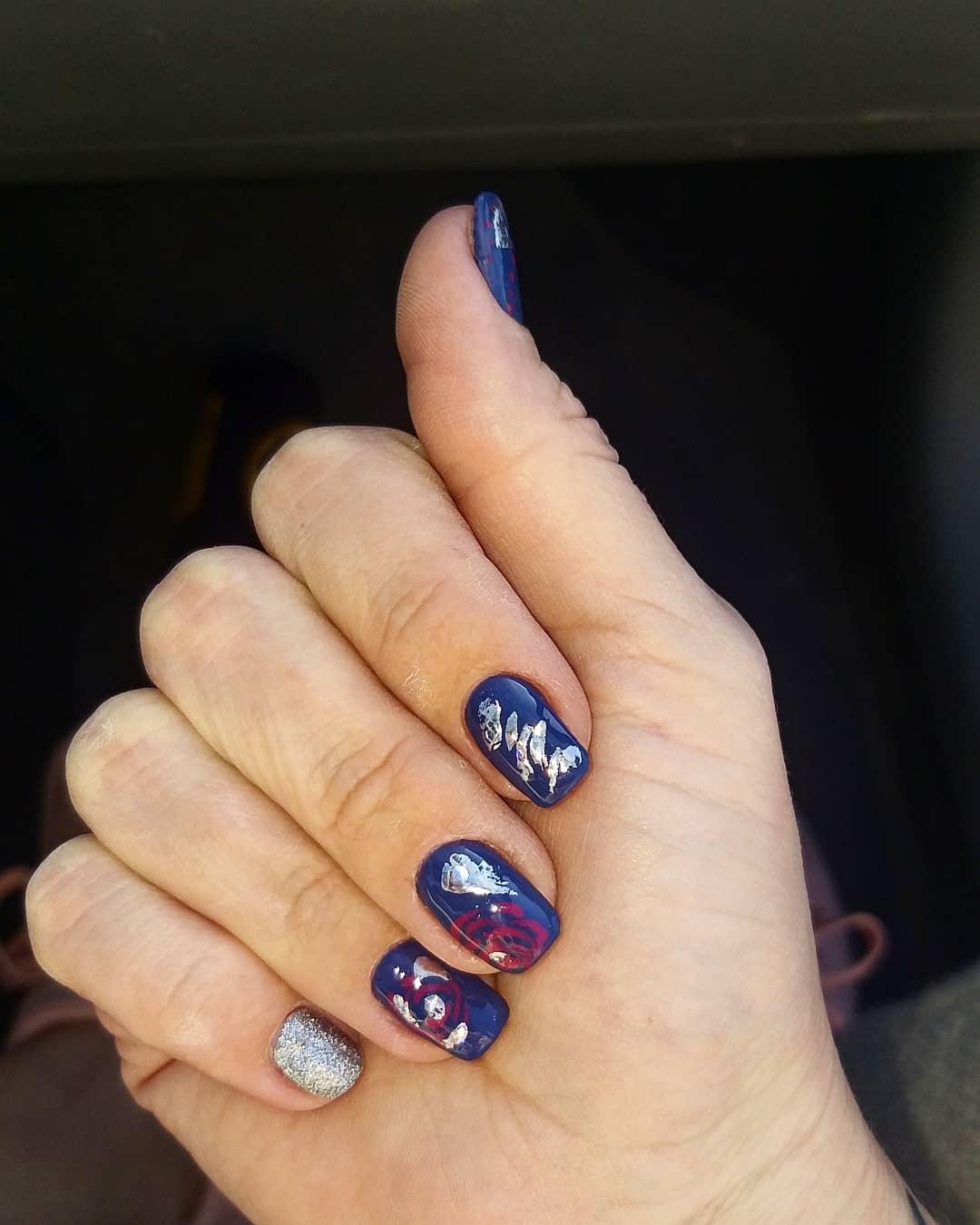 Маникюр в синем цвете с абстрактным рисунком и серебряными блёстками.