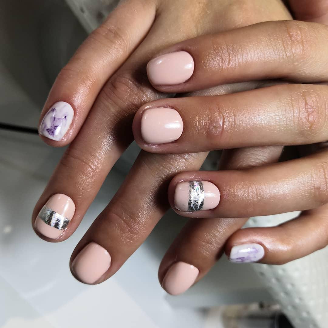 Маникюр с мраморным дизайном и серебряными полосками в персиковом цвете на короткие ногти.