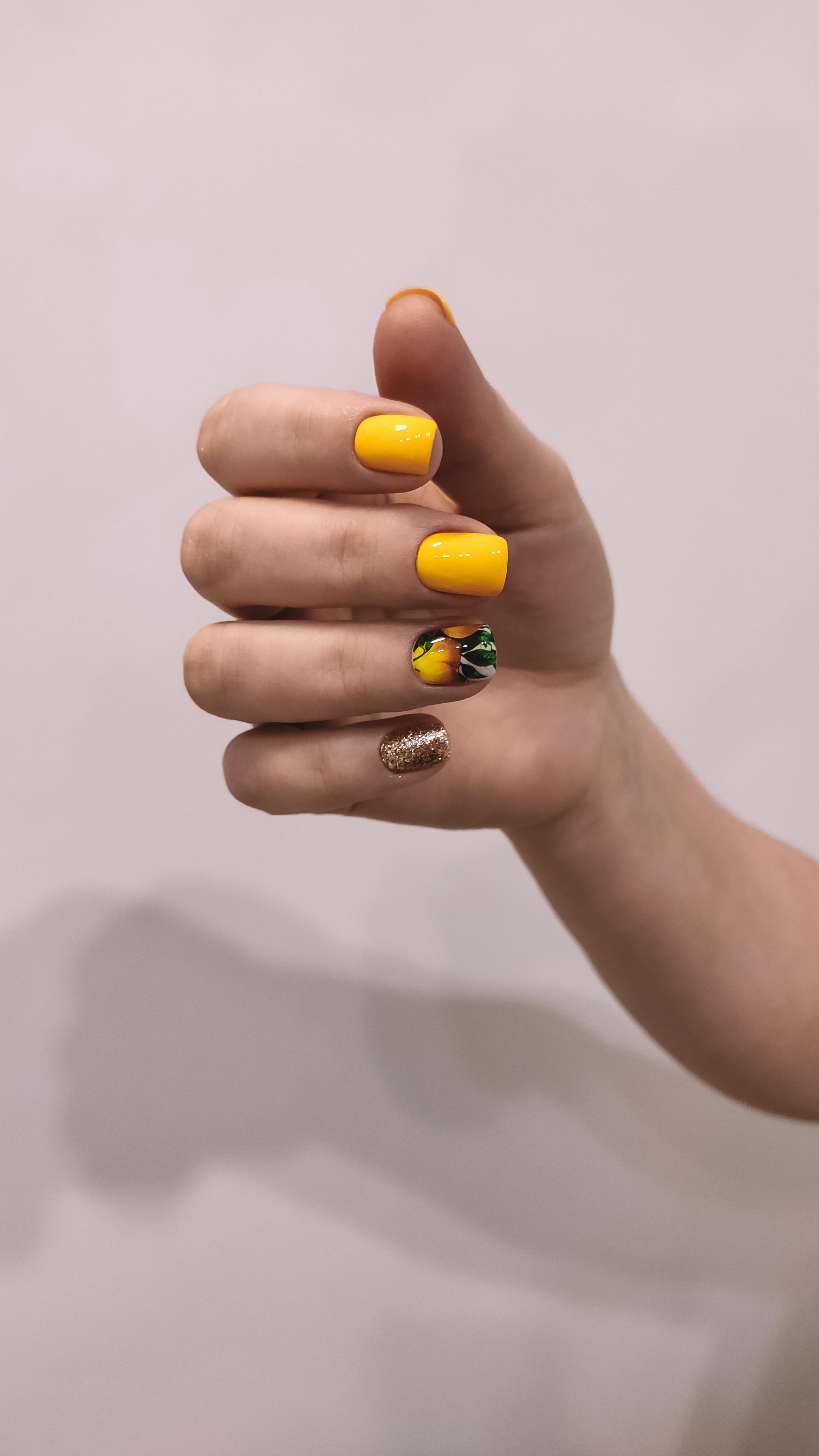 Маникюр с цветочным слайдером и золотыми блестками в желтом цвете.