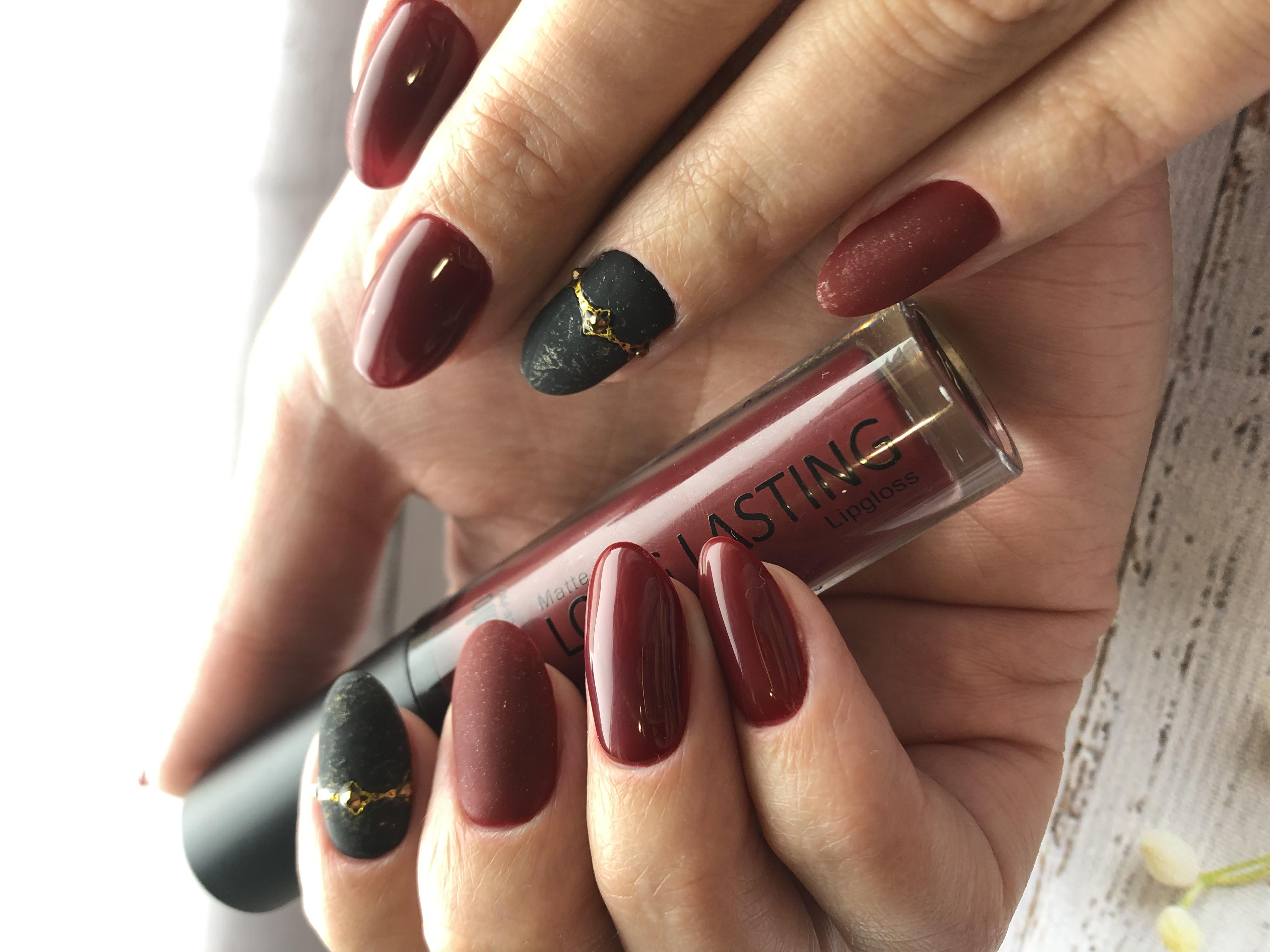 Маникюр с матовым дизайном и стразами в темно-красном цвете на длинные ногти.