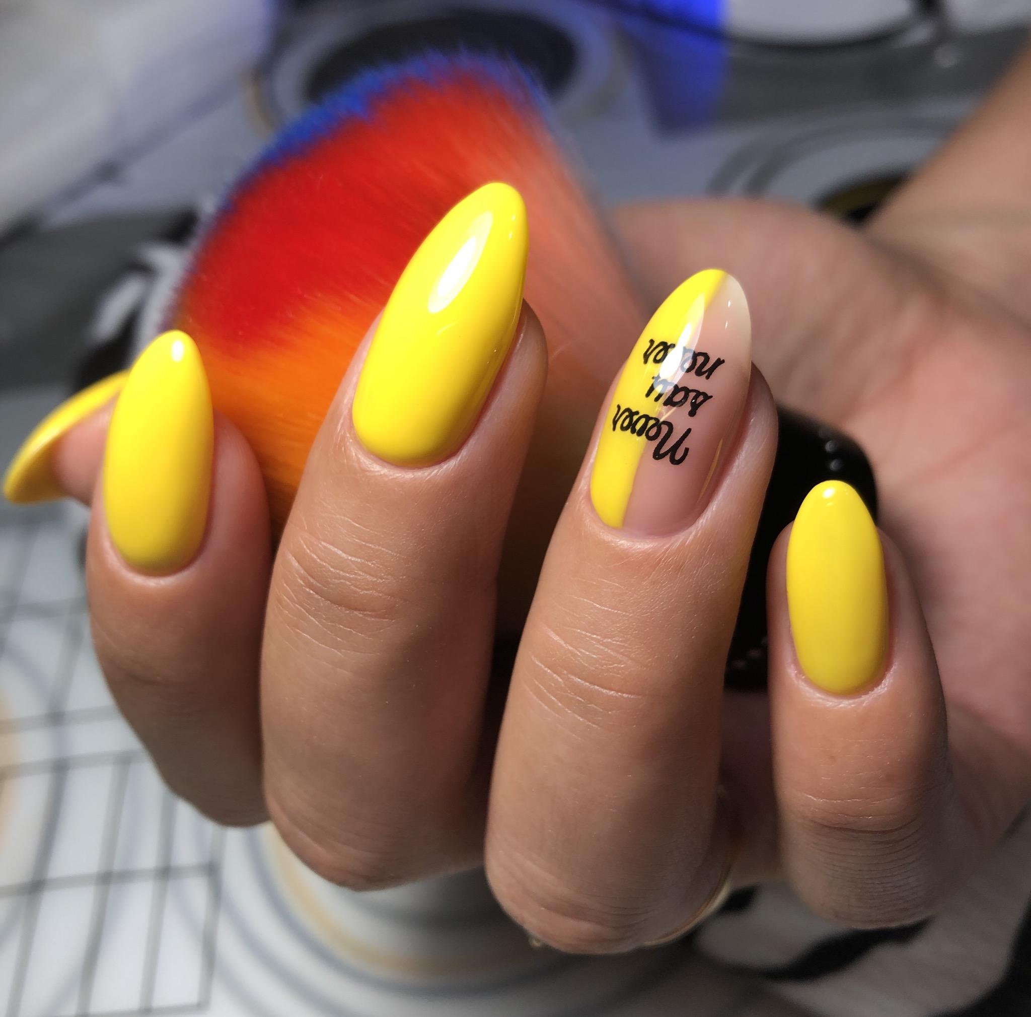 Маникюр с надписями в желтом цвете на длинные ногти.