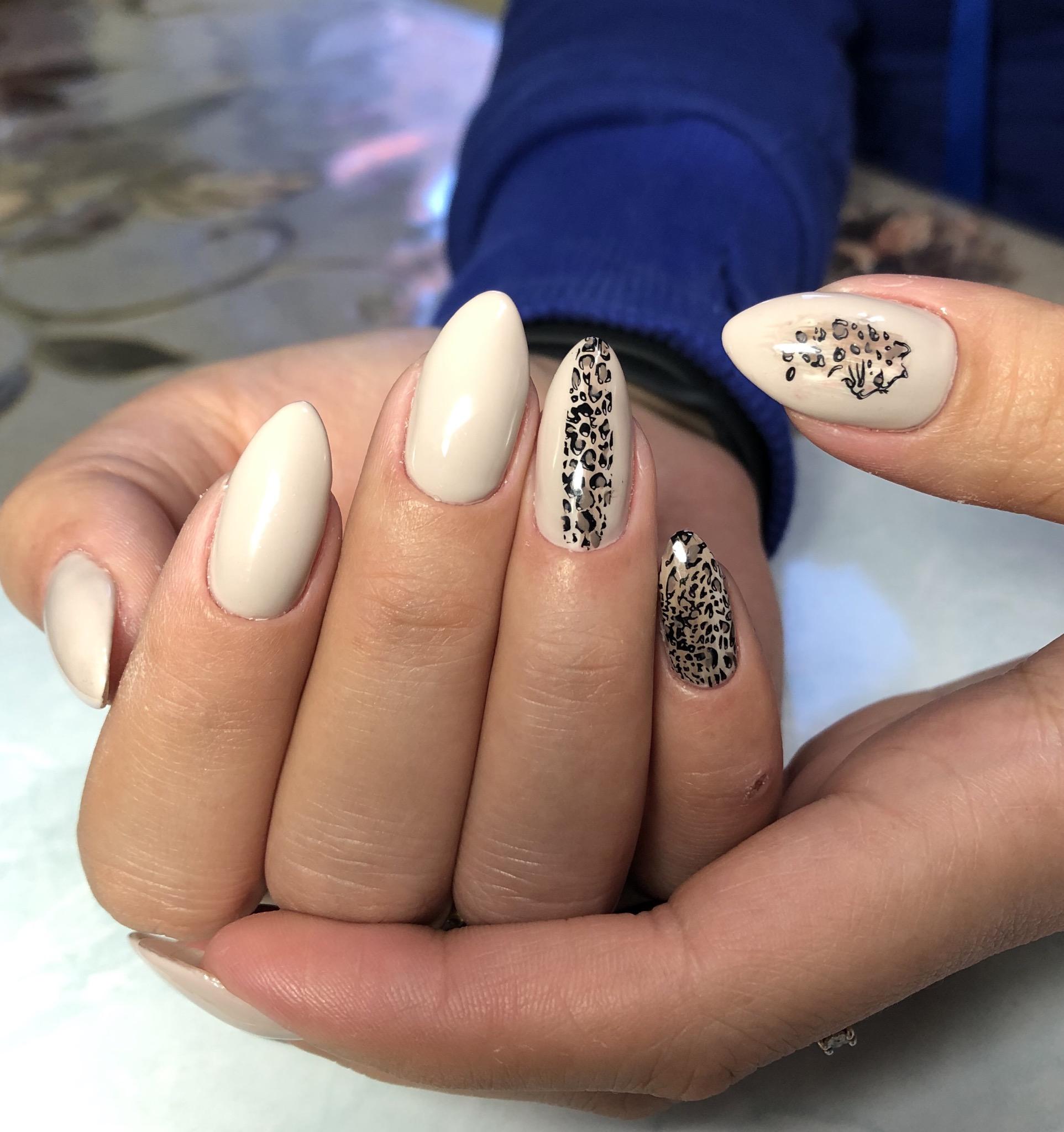 Маникюр с леопардовым принтом в молочном цвете на длинные ногти.