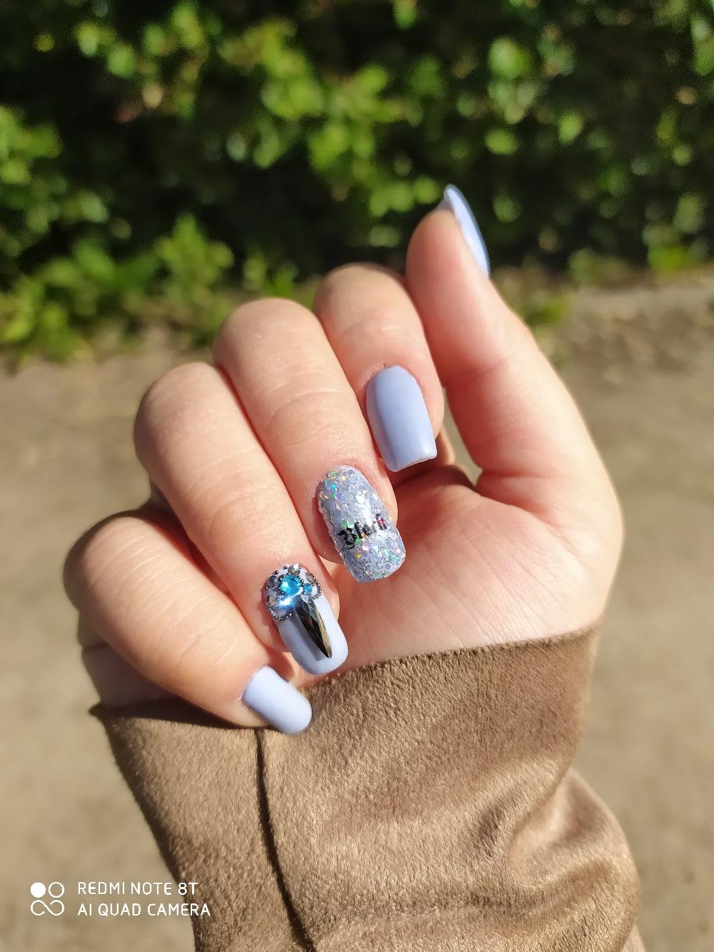 Маникюр с блестками, стразами и надписями в пастельных тонах на короткие ногти.