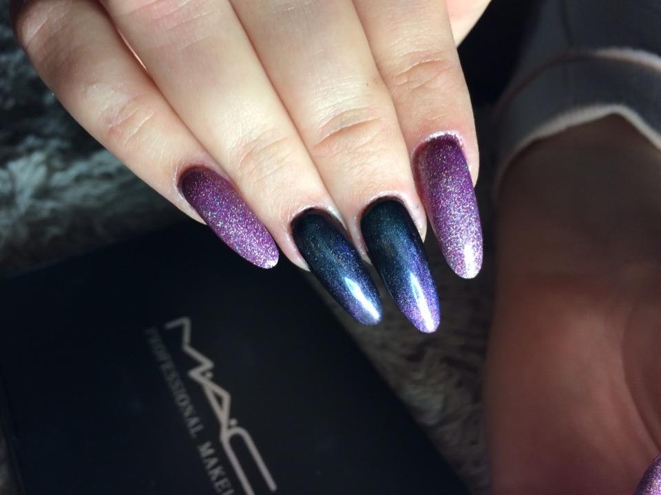 Маникюр с эффектом кошачий глаз и блестками в фиолетовом цвете на длинные ногти.