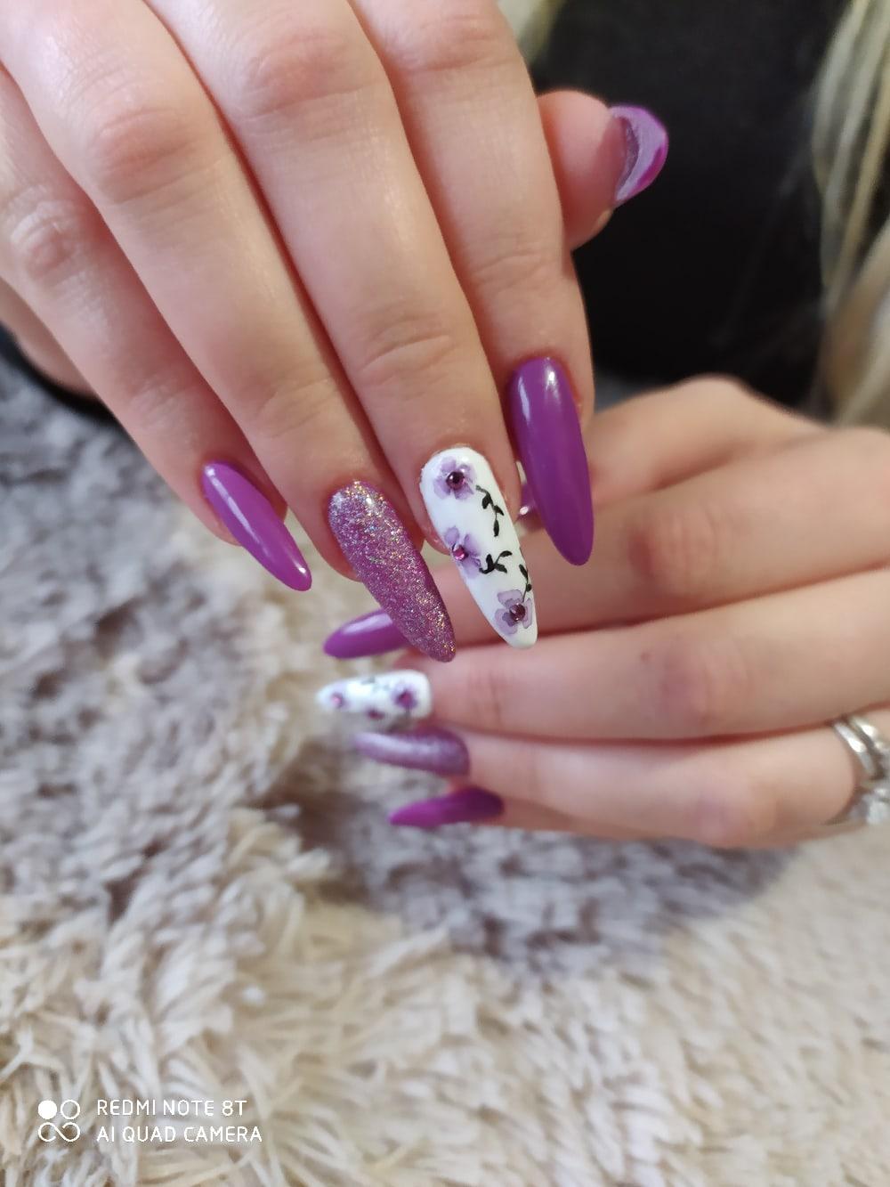 Маникюр с цветочным рисунком, блестками и стразами в фиолетовом цвете на длинные ногти.