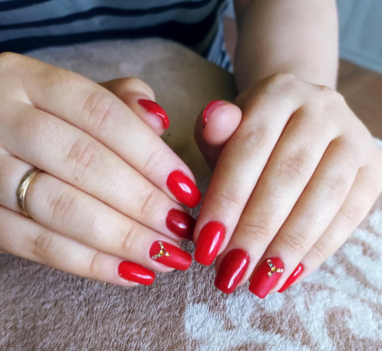 Маникюр со стразами в красном цвете на длинные ногти.
