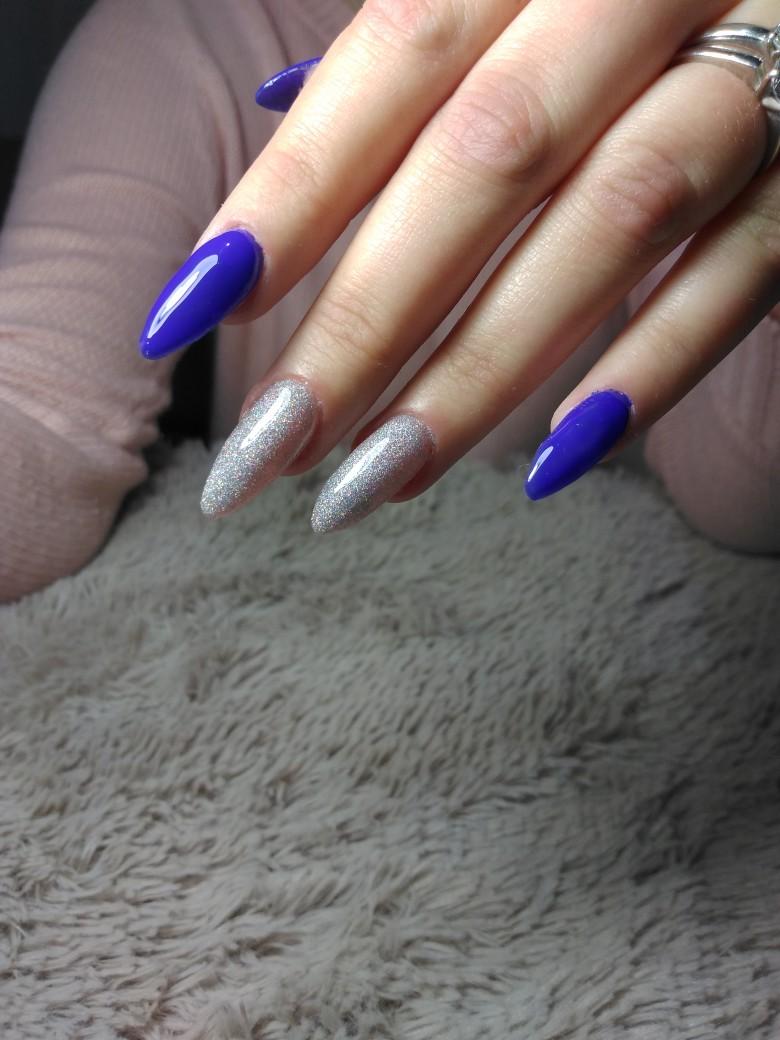 Маникюр с серебряными блестками в синем цвете на длинные ногти.