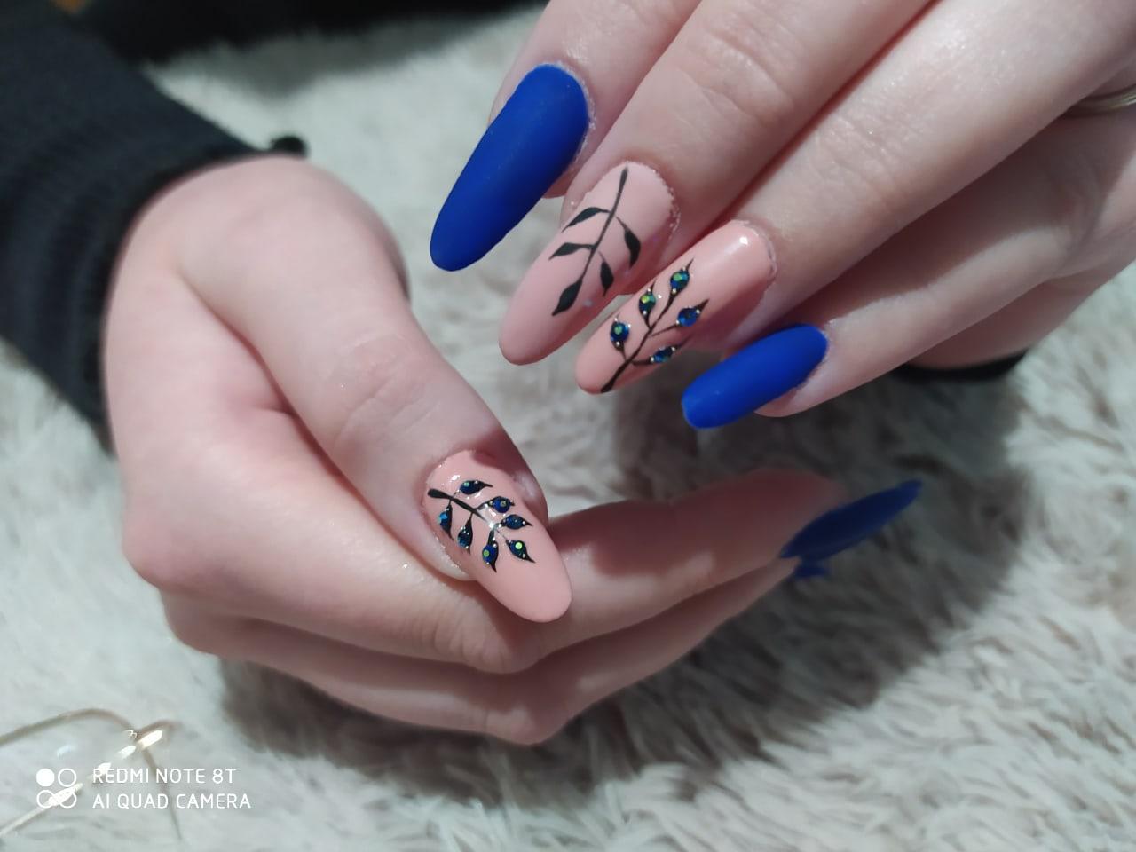 Матовый маникюр с растительным рисунком и стразами в синем цвете на длинные ногти.