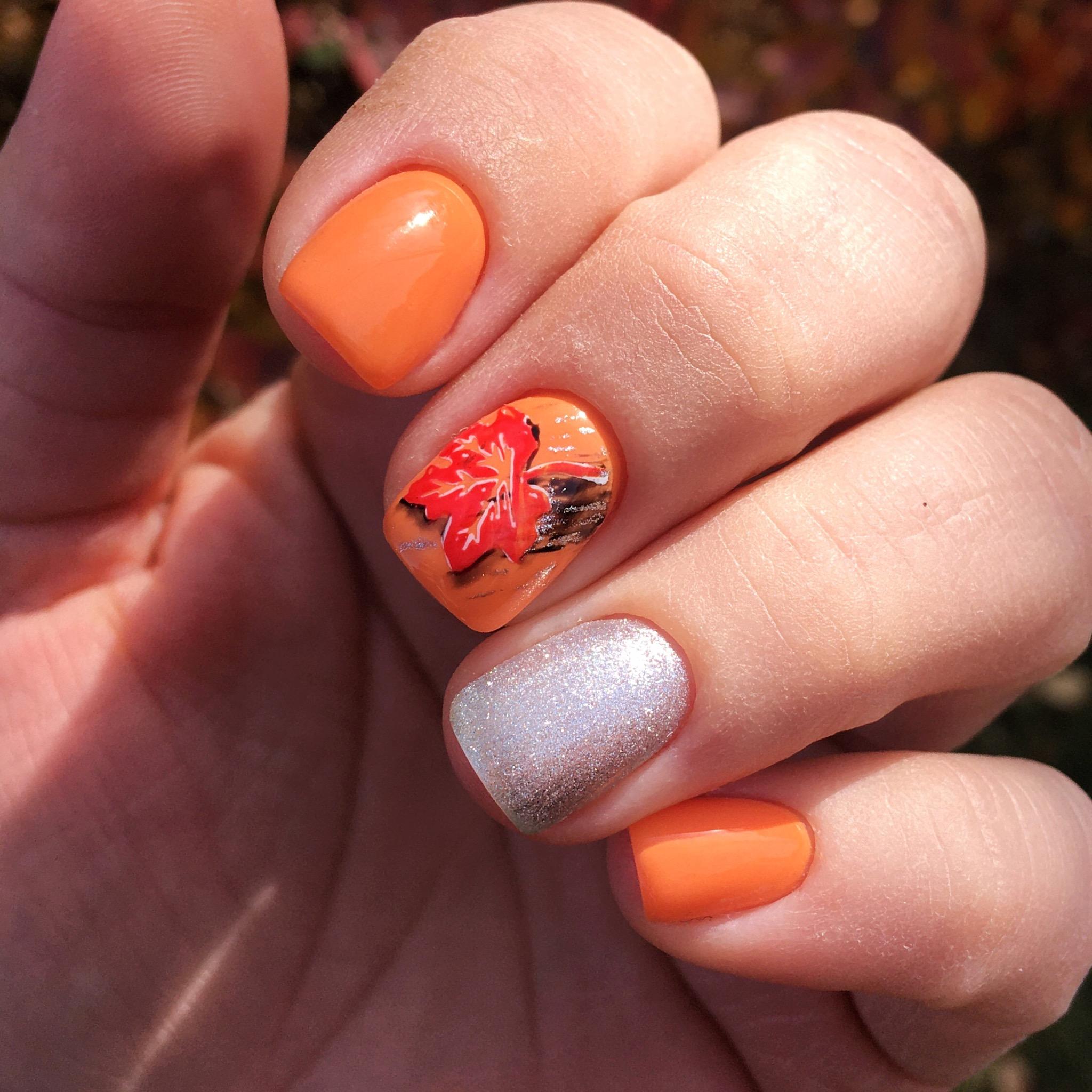Осенний маникюр с кленовым листом и серебряными блестками в оранжевом цветен а короткие ногти.