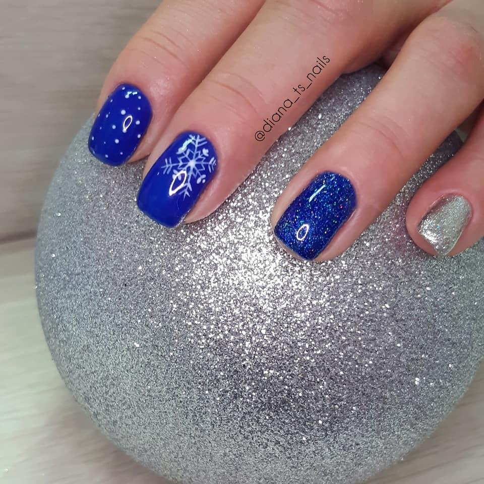 Маникюр со снежинкой и серебряными блестками в синем цвете.