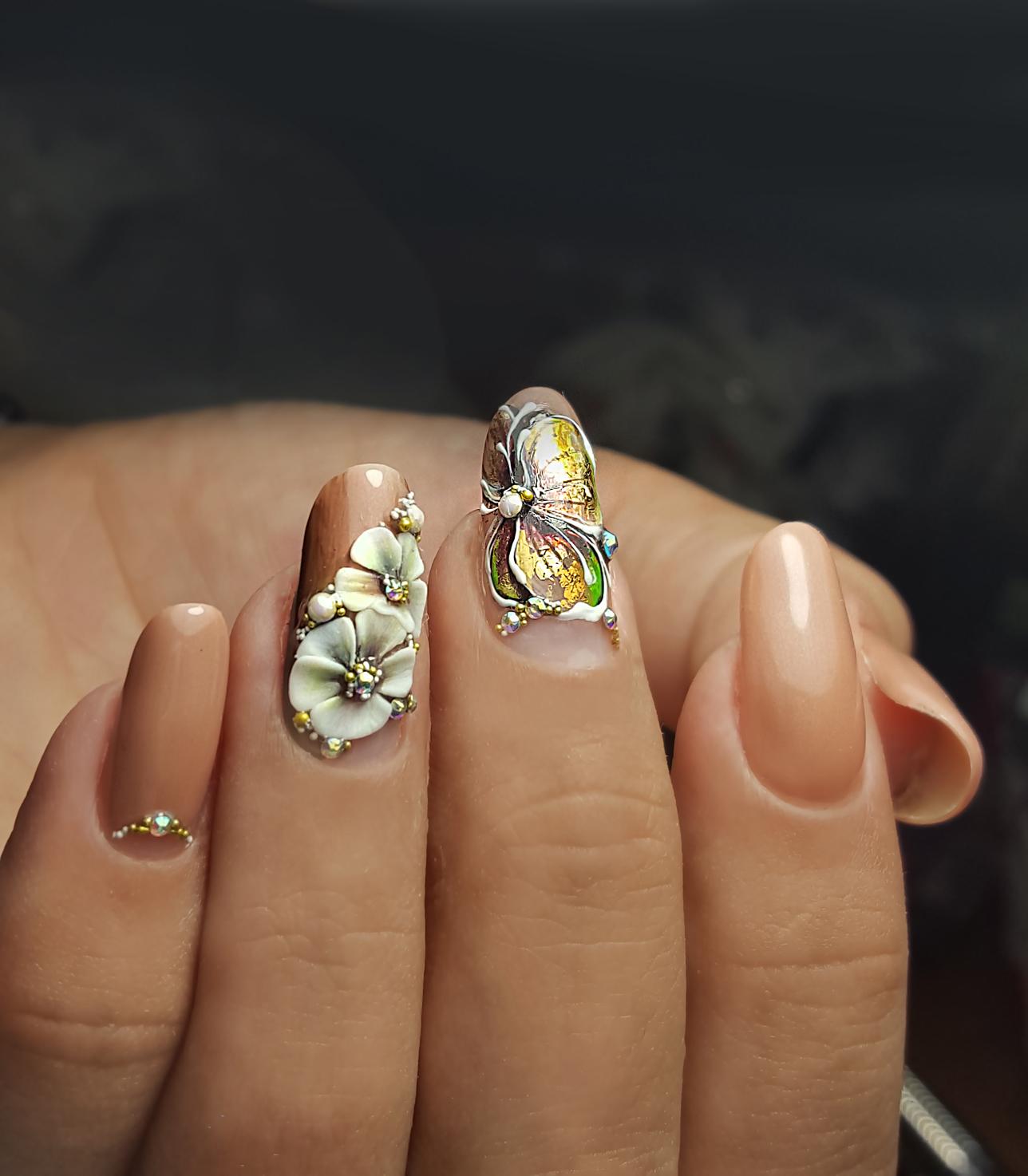 Маникюр с цветочной лепкой и стразами в персиковом цвете.