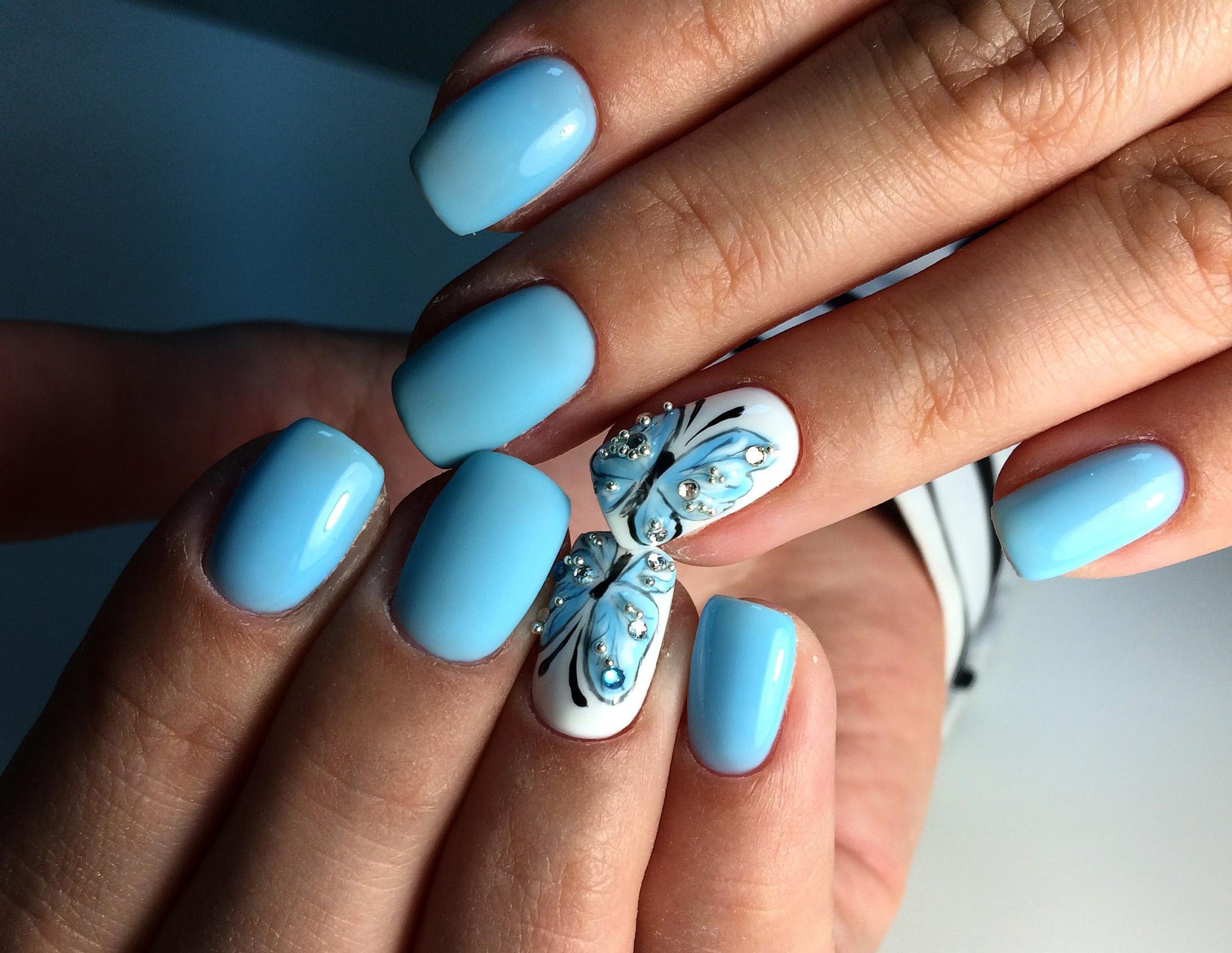 """Маникюр в голубом цвете с белым дизайном, рисунком """"бабочка"""" и стразами."""