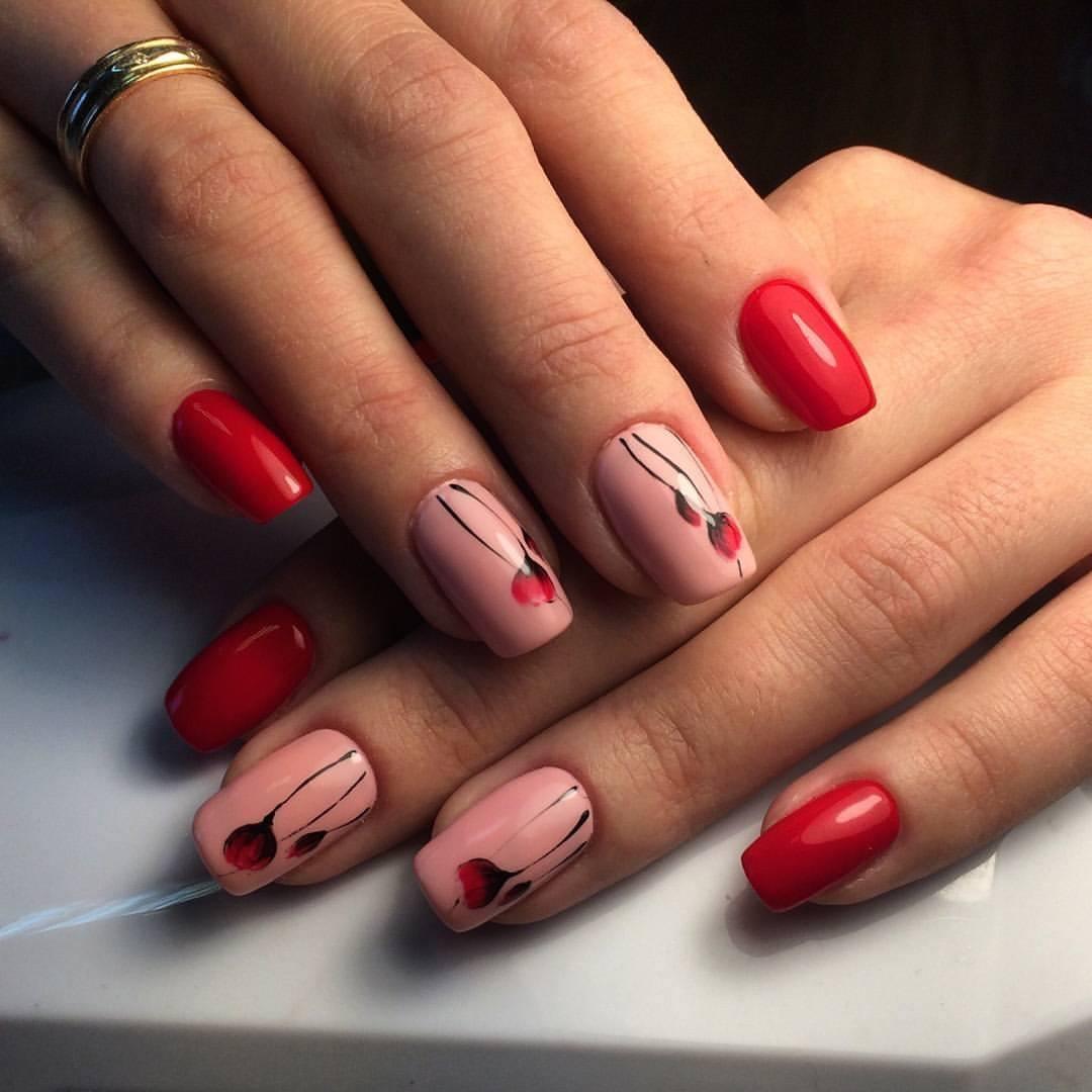 Маникюр в красном цвете с розовым дизайном и цветочным рисунком.