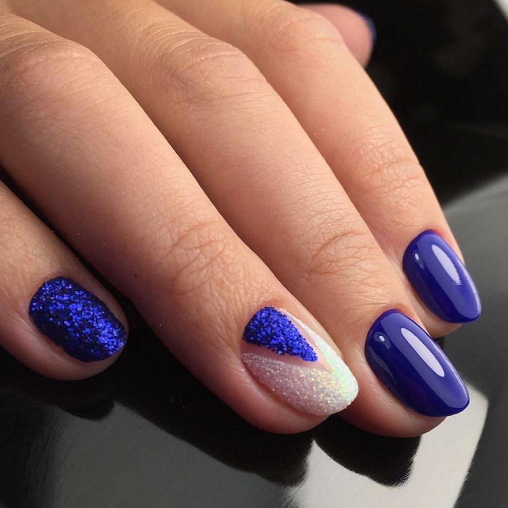 Маникюр в синем цвете с блестящим песочным дизайном.