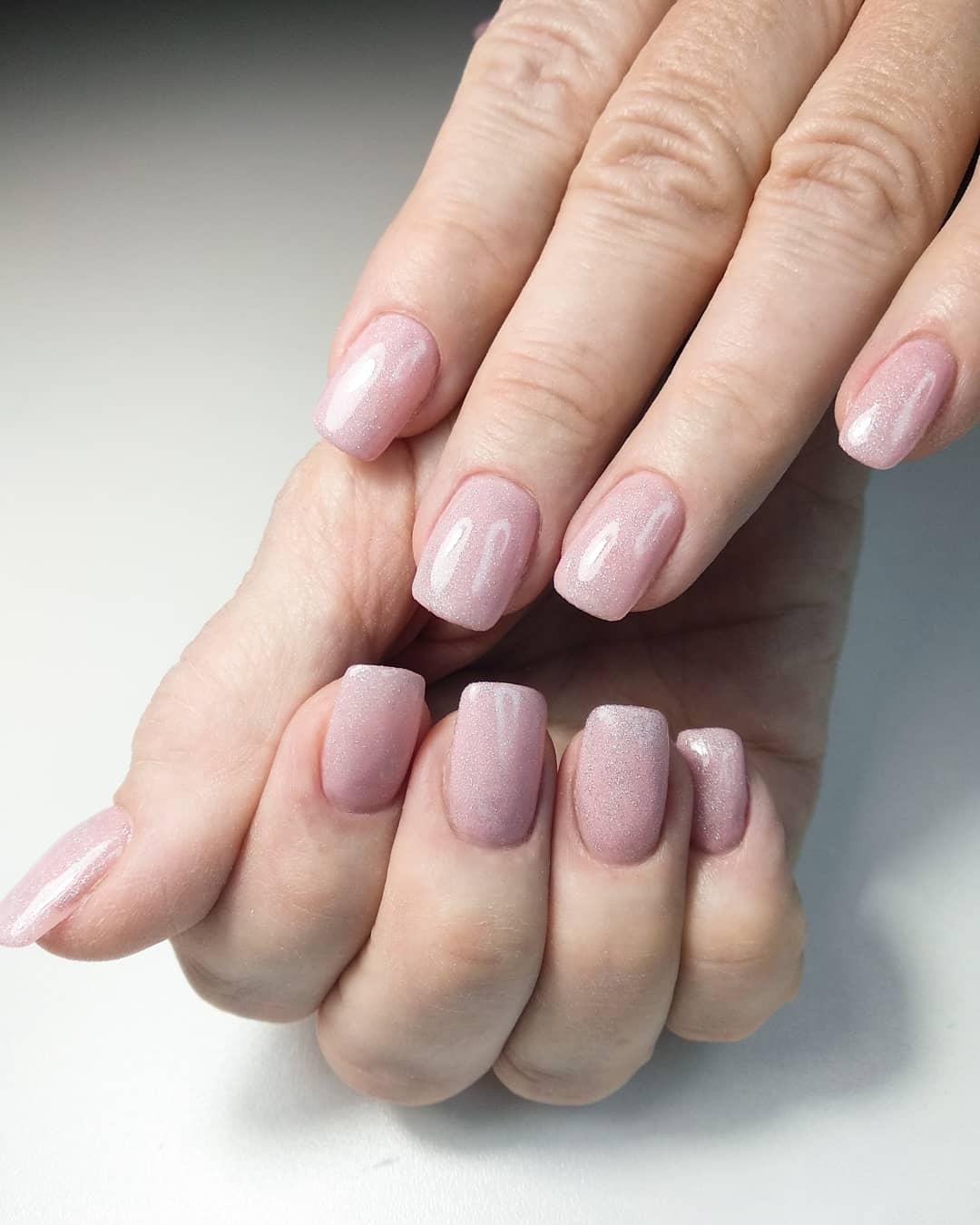 Полупрозрачный маникюр в розовом цвете с блёстками.