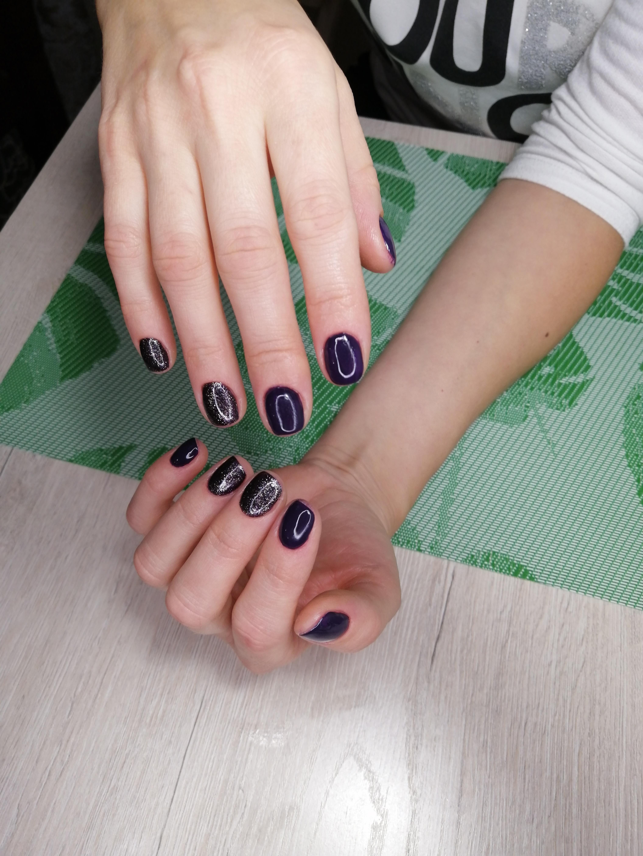 Маникюр чёрно-синем цвете с серебряными блёстками.