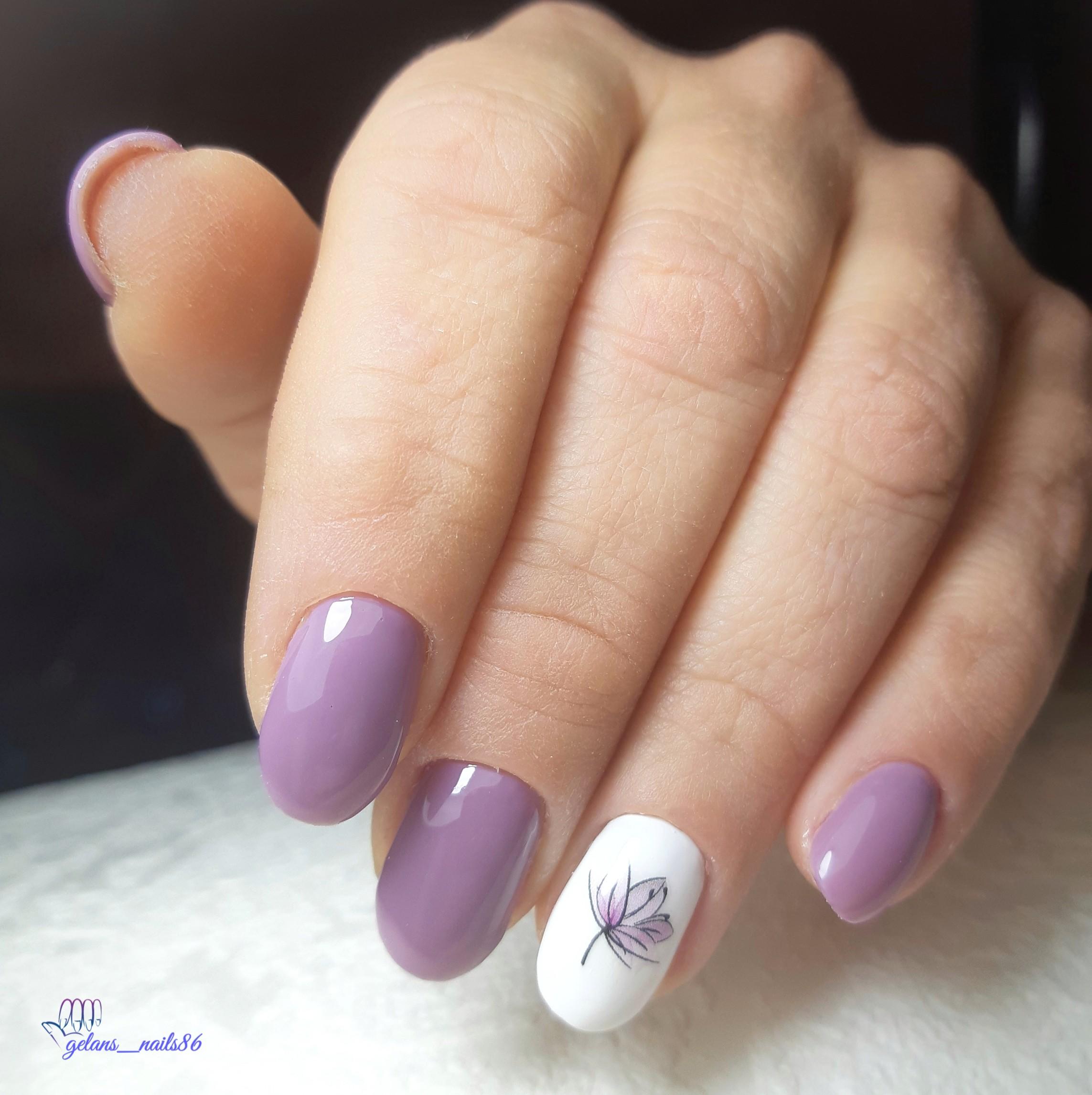 Маникюр в сиреневом цвете с белым дизайном и цветочным слайдером.